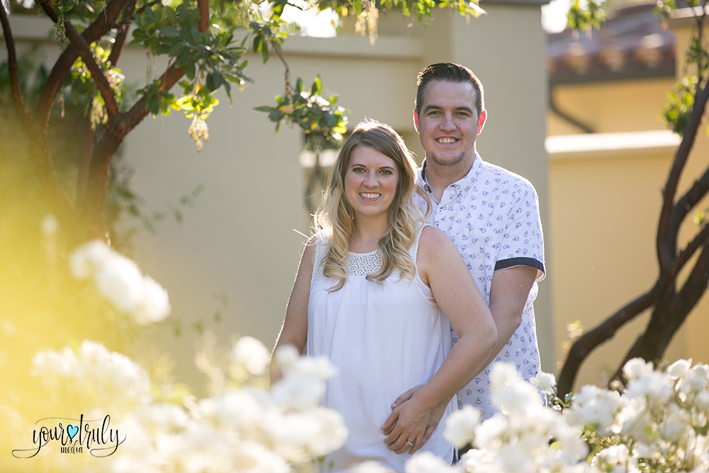 Family photography session - Orange County, CA - Husband and wide pose among white flowers.