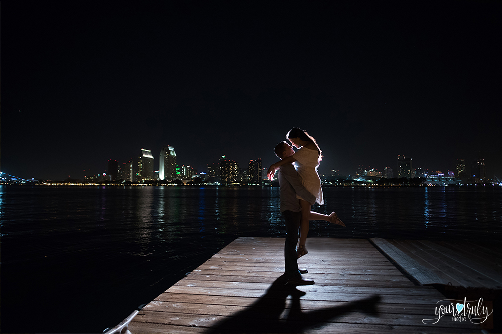 A couple on a pier at night with the San Diego skyline in the background.