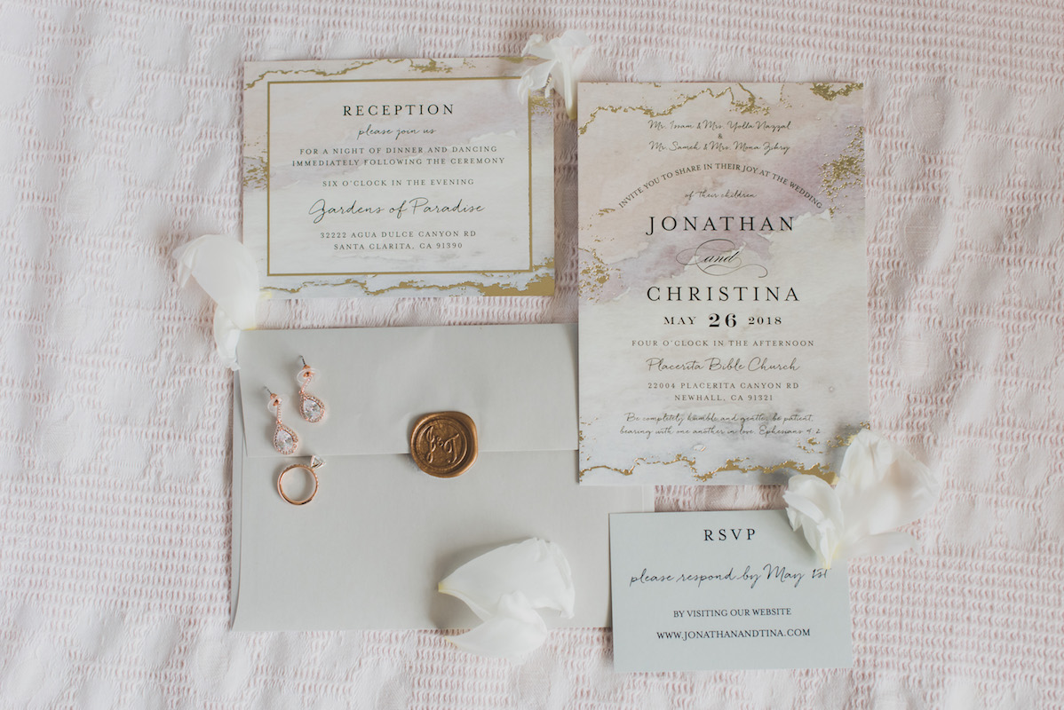 A wedding invitation set including the invite, the rsvp card, the reception card, and an envelope featuring a wax seal.