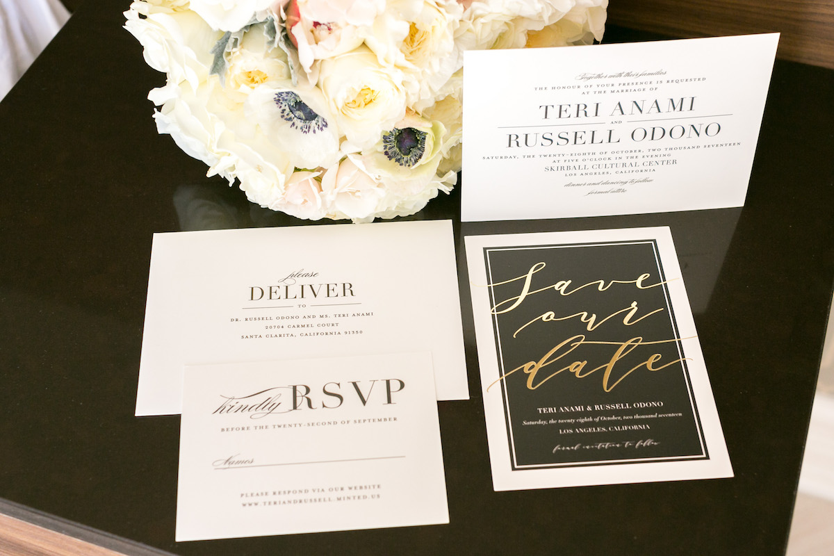 A wedding invitation set on a black marble table featuring a bright white bouquet of roses.