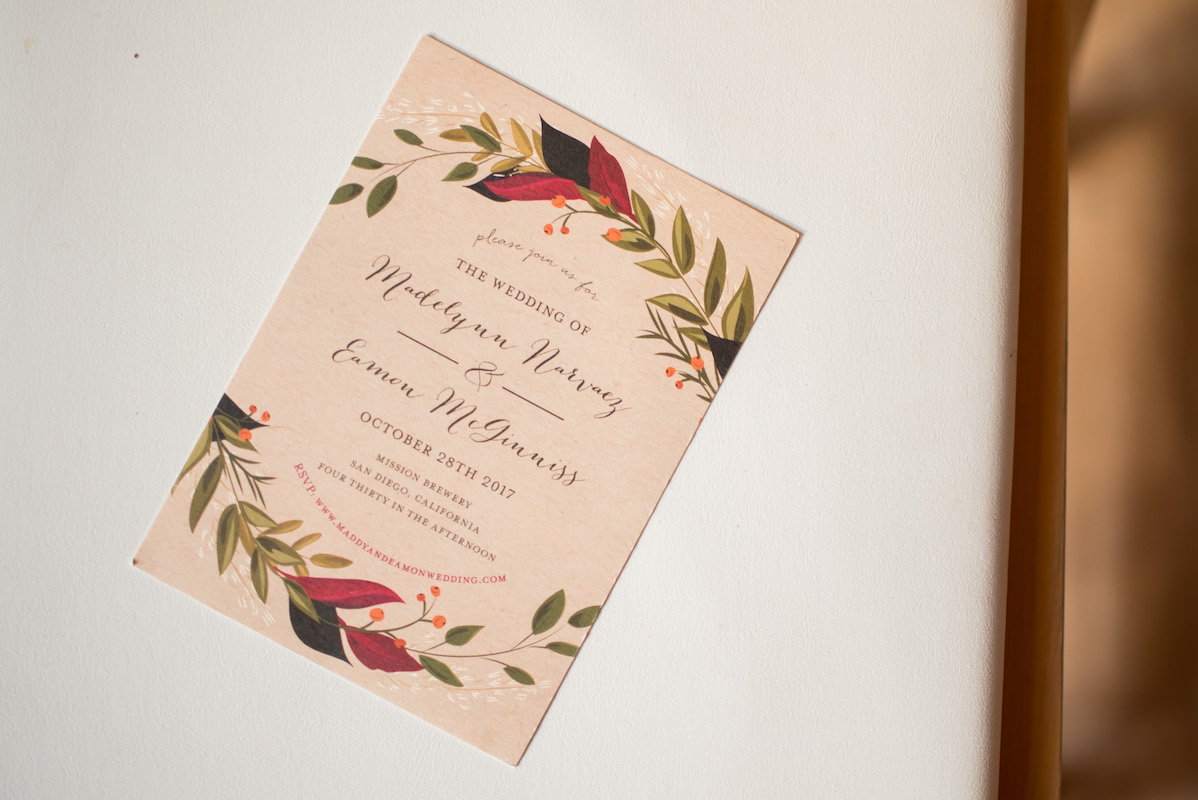 A simple yet elegant wedding invitation featuring laurels on a faded pink card.