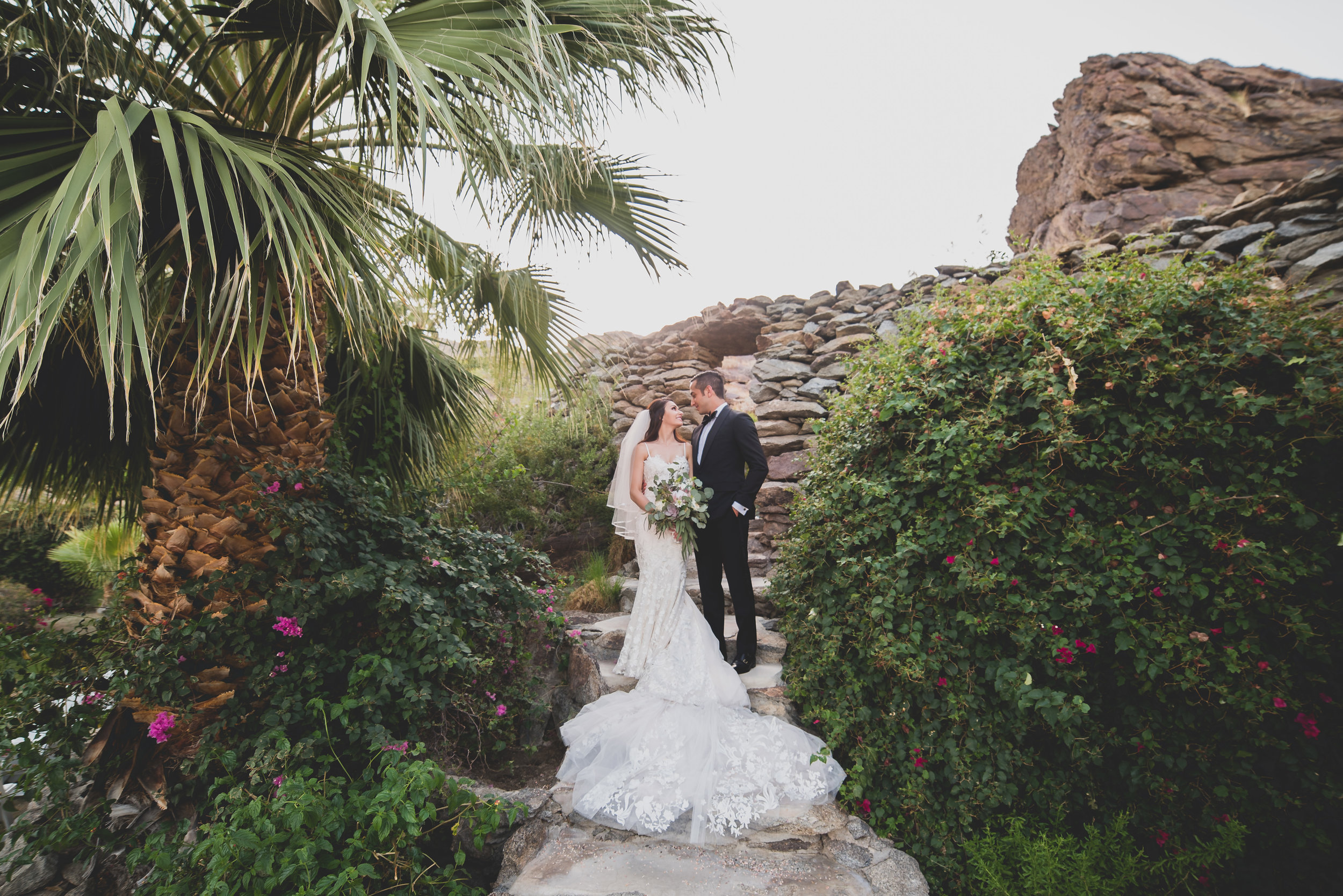Bride in a flowing white dress and groom in a classic tux surrounded by natural lush greenery and a palm tree.