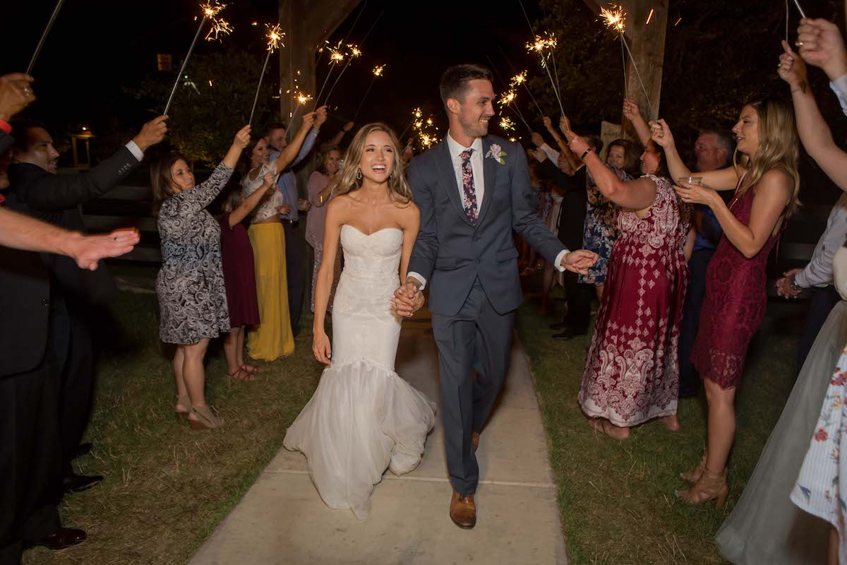A newlywed couple making their grand exit through a sea of sparklers.