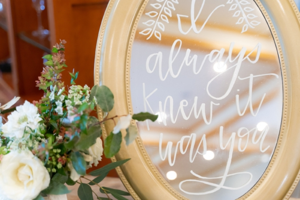 """Bridal suite with a decorated mirror reading, """"I always knew it was you."""""""