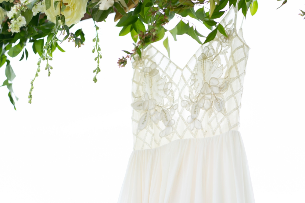 A wedding dress hanging outdoors from a banister decorated with flowers and greenery.