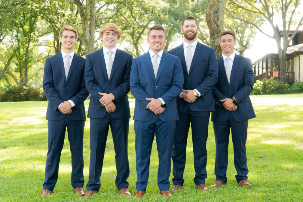 The groom standing outdoors with his groomsman on a bright green lawn.