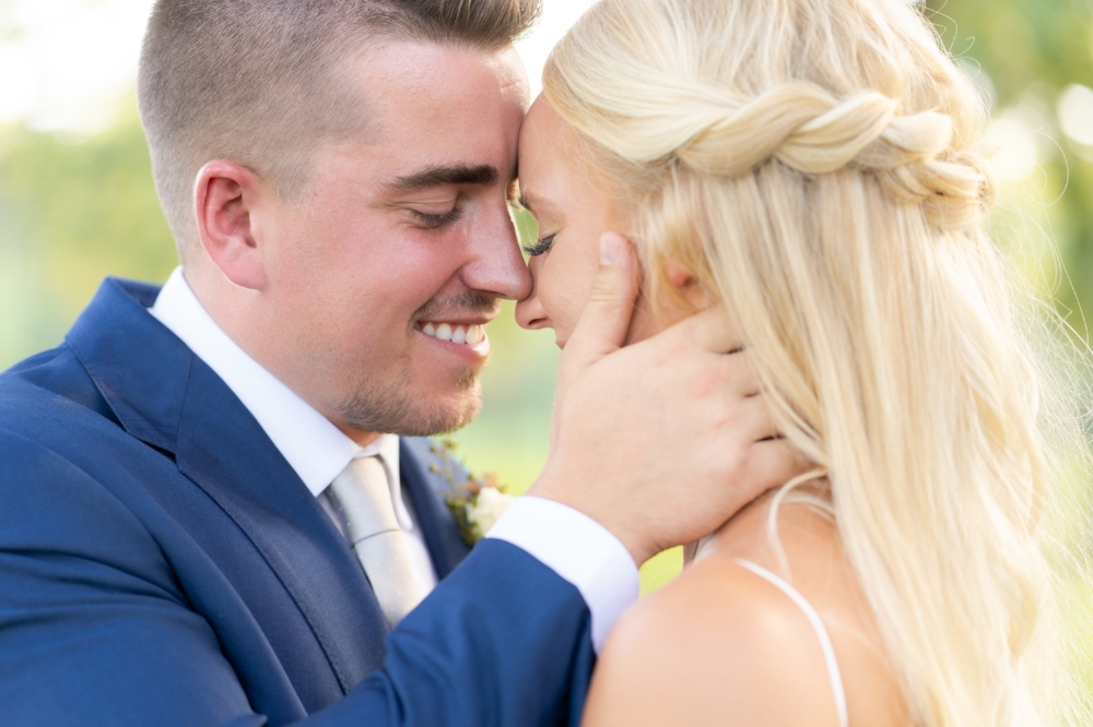 Bride and groom smiling while touches noses.