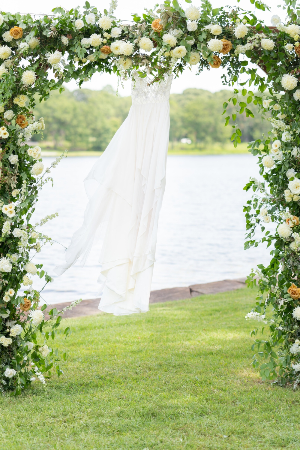 Wedding hanging from a floral archway in front of Lake Athens, TX.