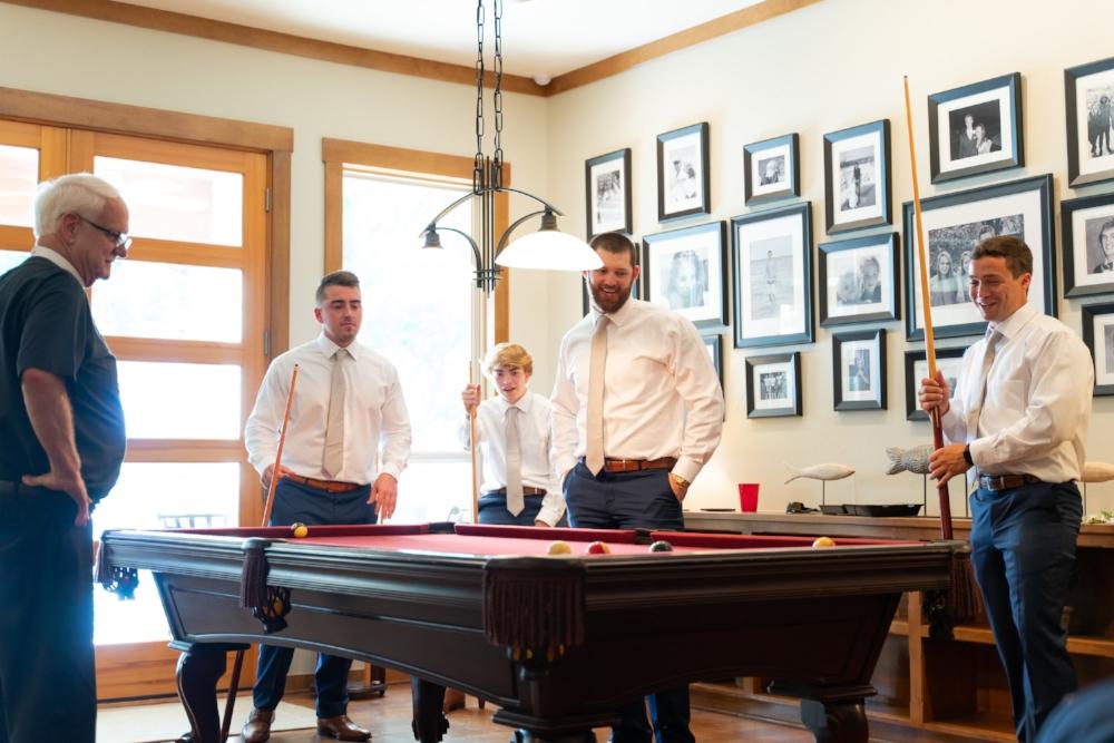 Groomsman playing billiards prior to the wedding.