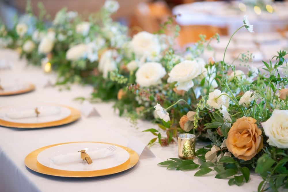 The bridal party table decorated with white, gold-rimmed plates and a floral table runner of white and orange roses.