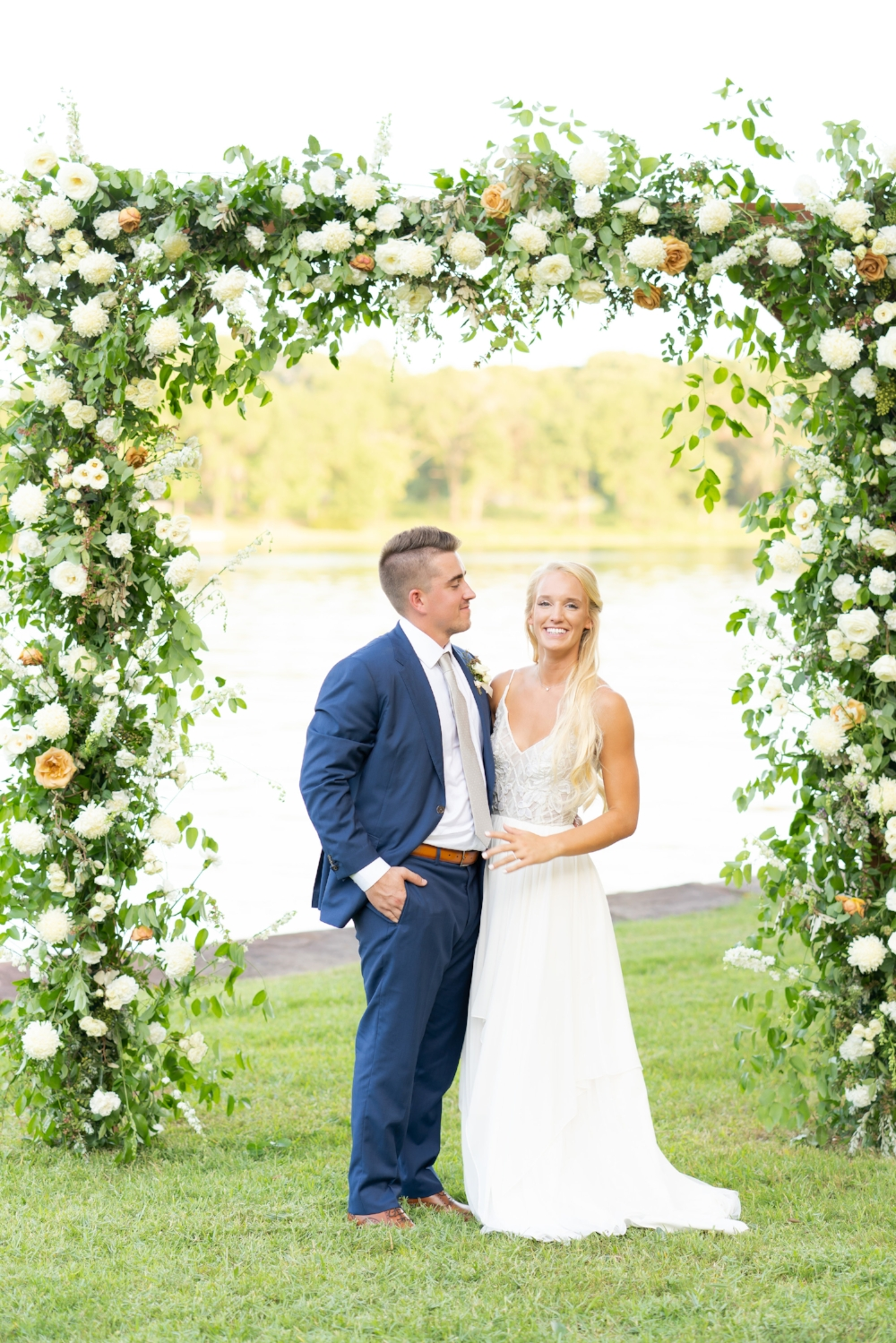 Bride and groom standing next to each other under a large floral arch.