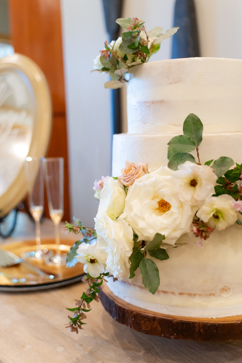 A white wedding cake sitting atop a circular wooden base decorated with white roses.
