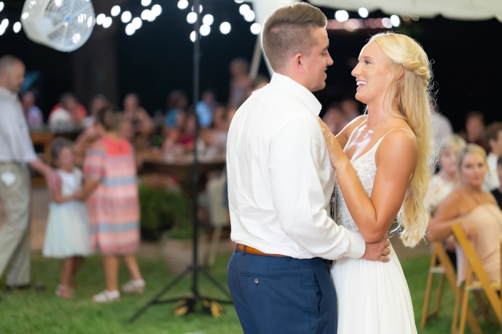 The groom with his jacket off, and the smiling bride during their first dance at an outdoor evening reception.