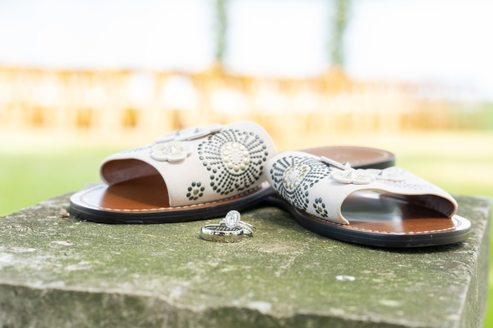 The brides white sandals and the wedding bands perched atop a square stone.