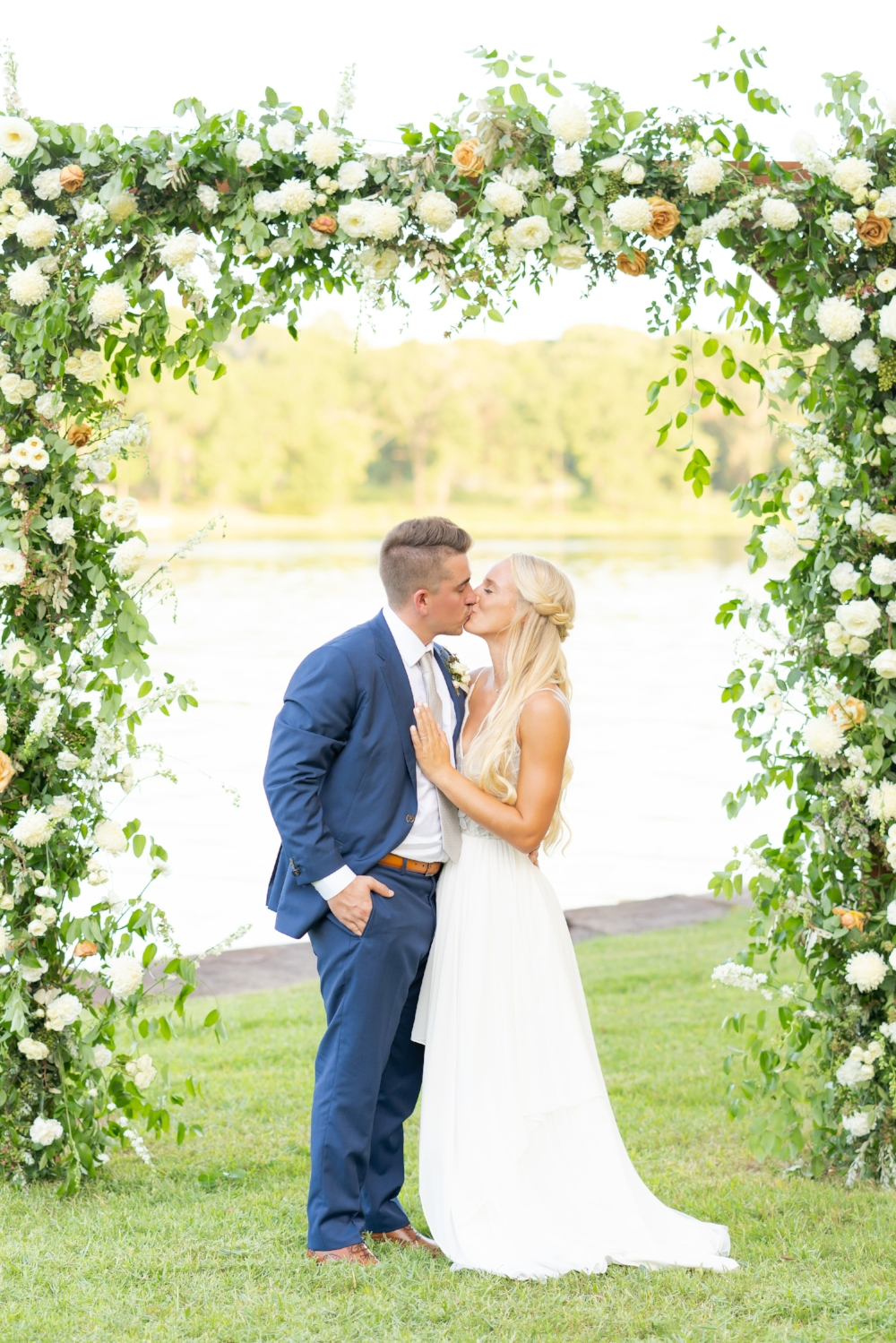 Bride and groom kissing under a large floral arch in front of Lake Athens.