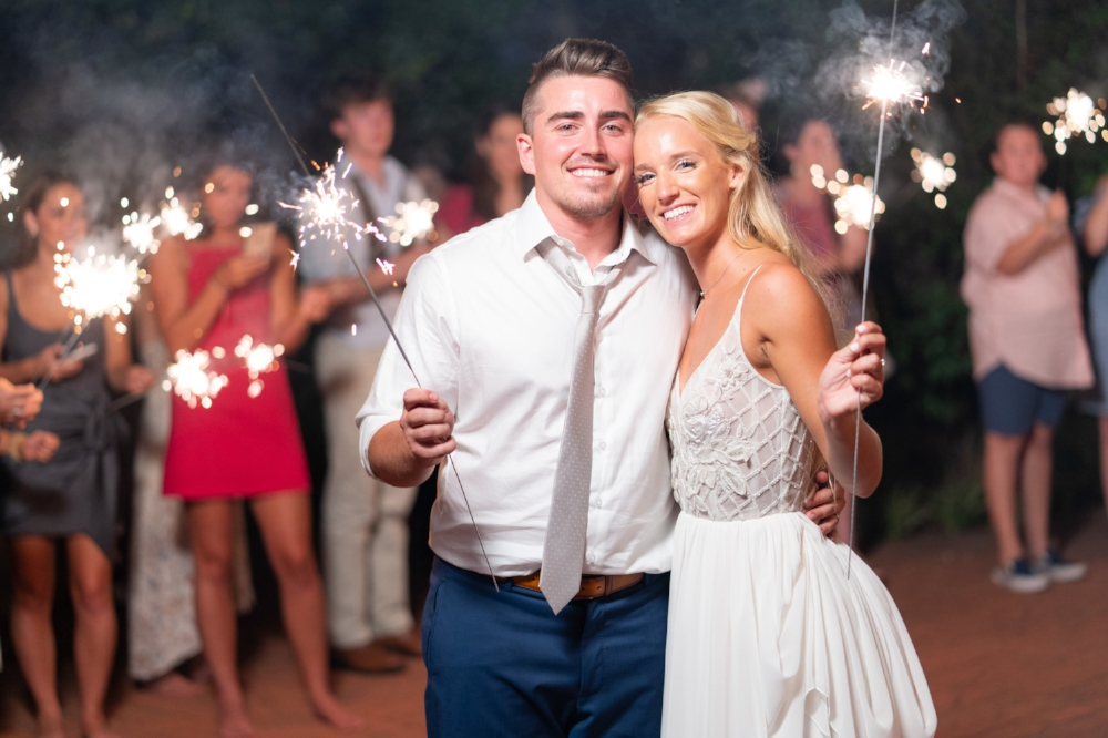 Bride and groom holding a pair of sparklers with their guests cherring in the background as they make their grand exit.