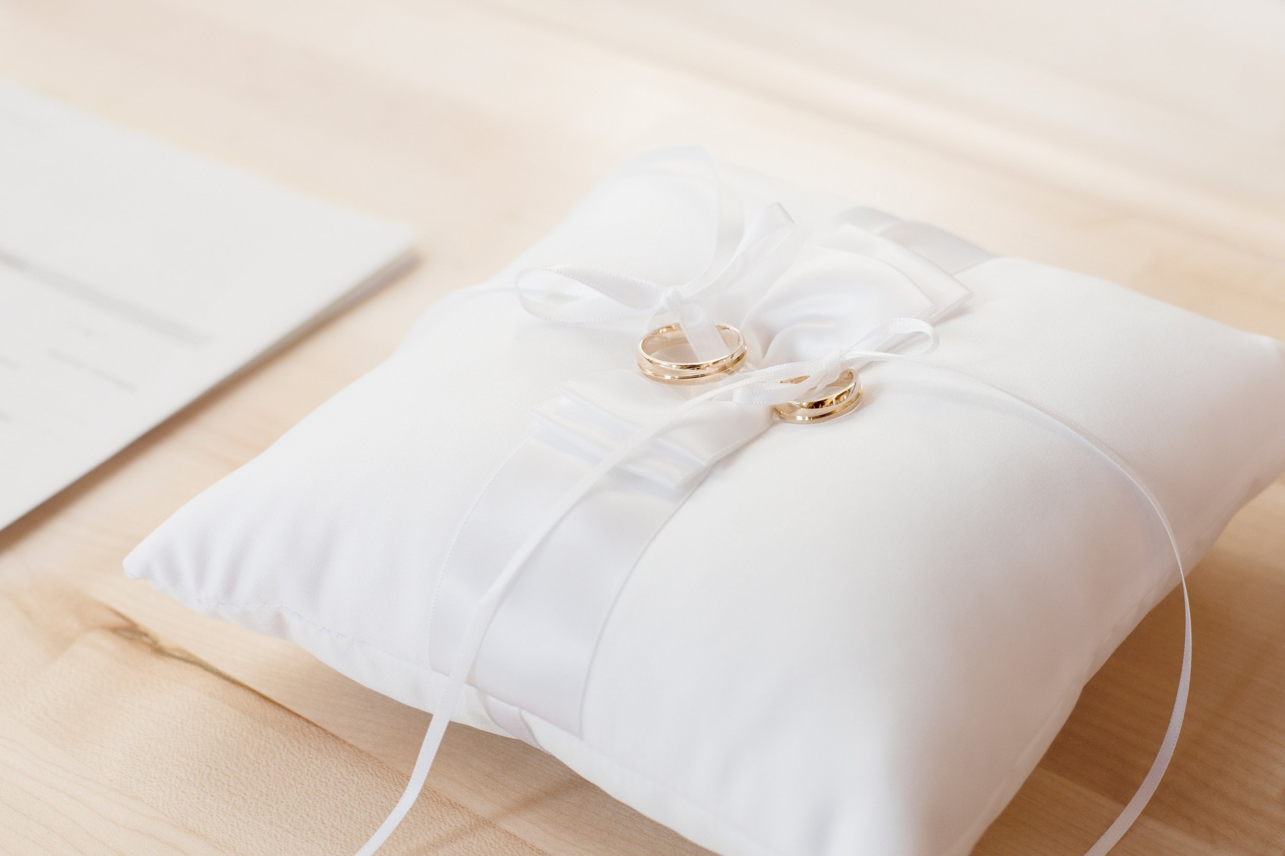 White ring cushion with two gold wedding bands attached by white ribbons.