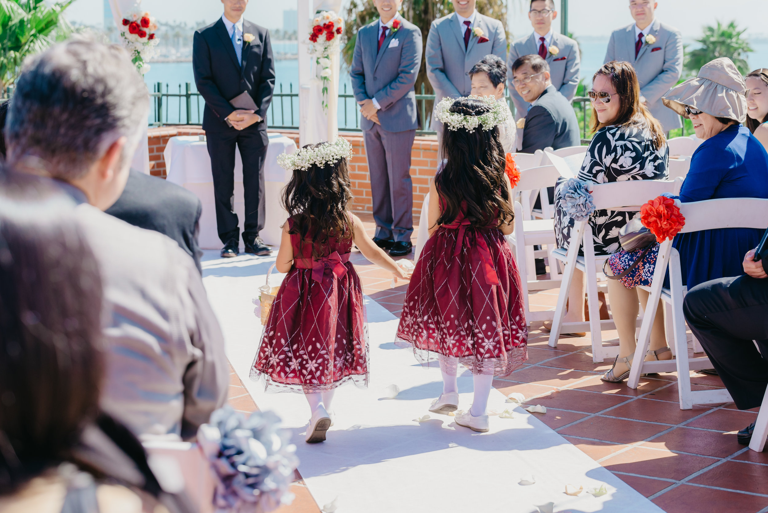Two young sisters in red dresses and flower crowns throwing flowers as they walk down the aisle together as flower girls.
