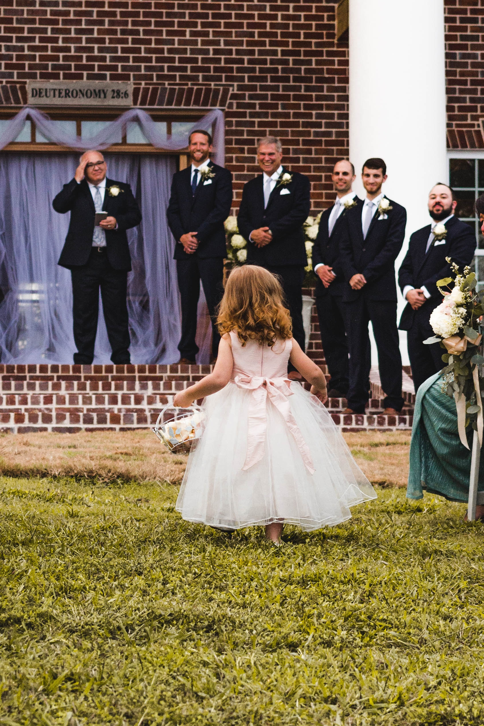 Little flower girl walking down the aisle to the smiles of the groomsman.