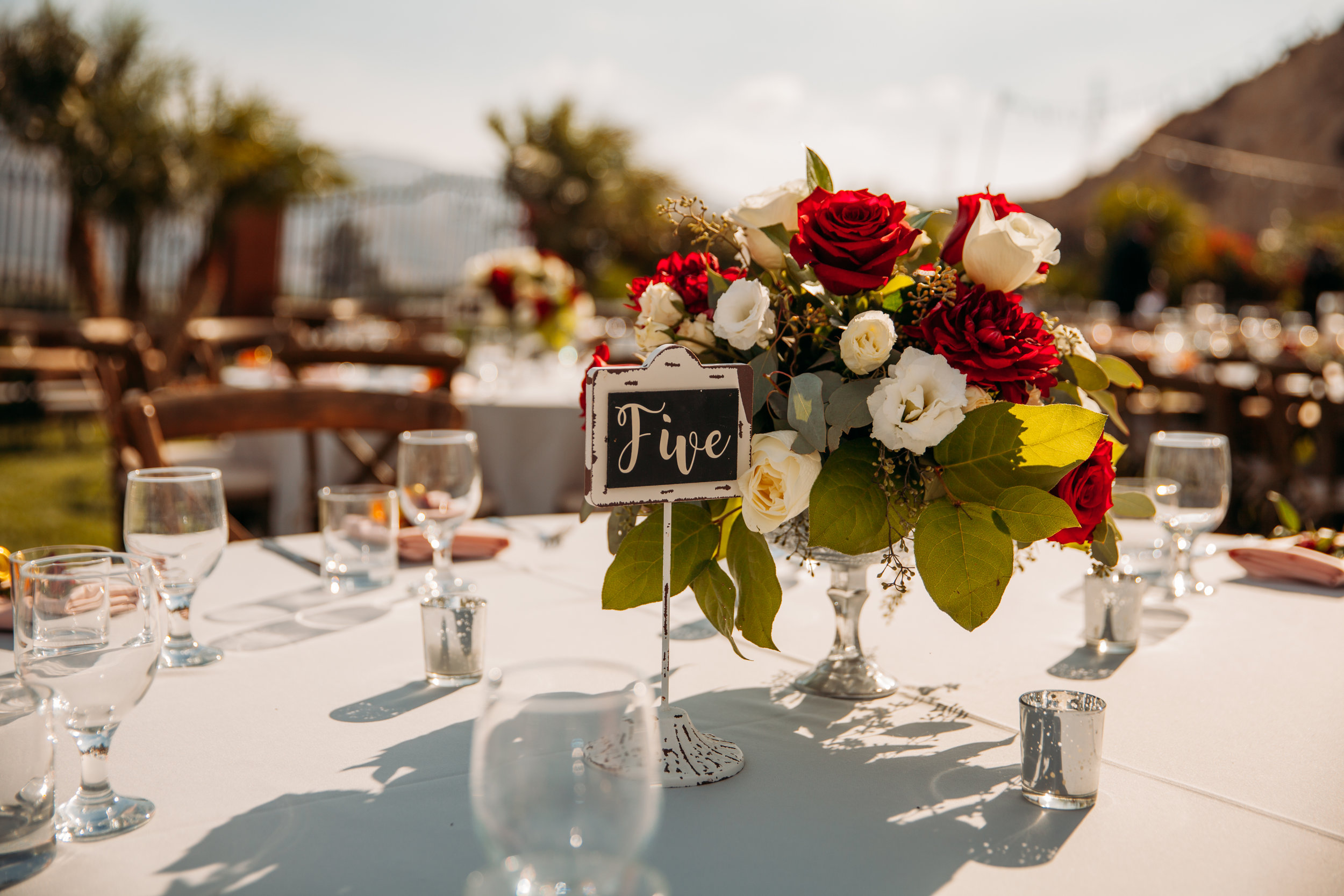 A rose and acorn studded DIY centerpiece on a white table at an outdoor reception.