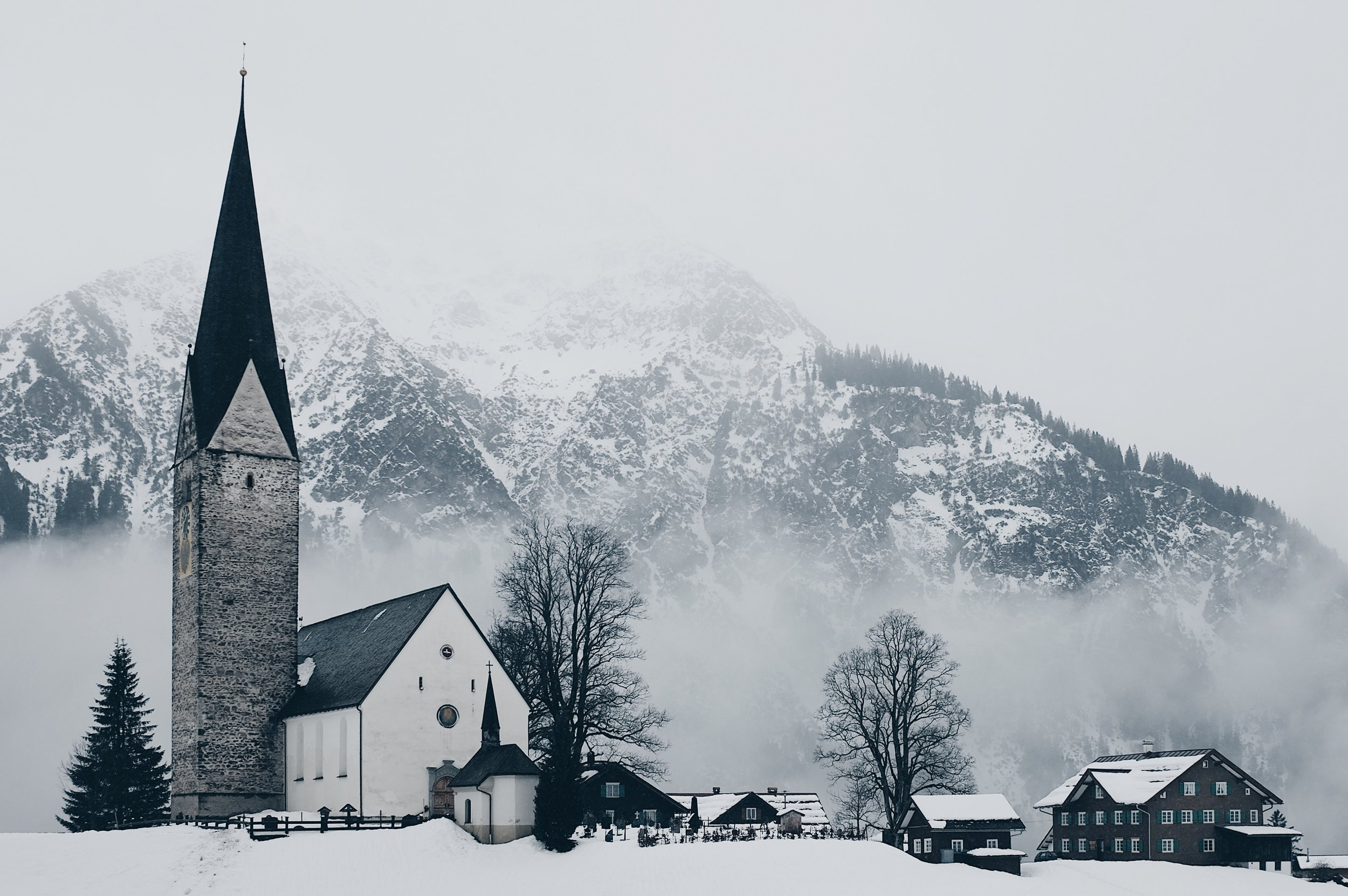 A stone chapel on a snowy winter night, with hilly mountains in the background.