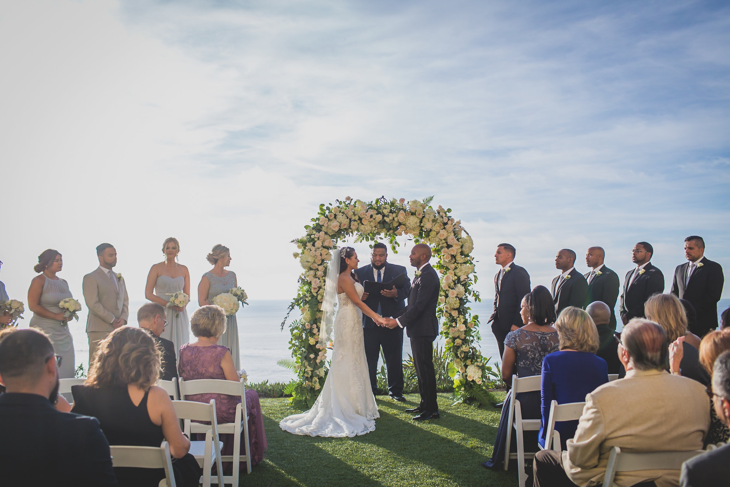 A wedding ceremony on a grassy cliff overlooking the ocean.