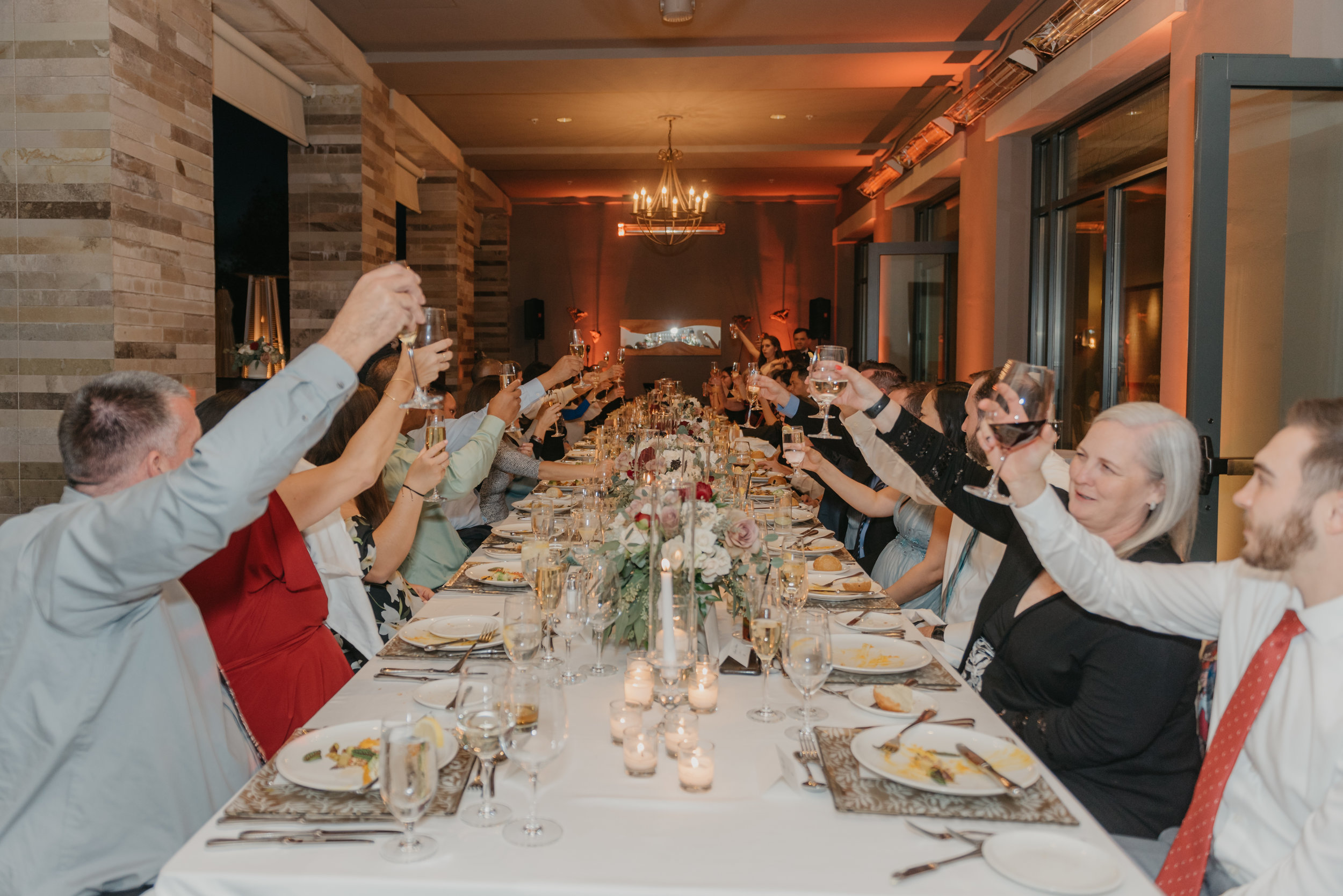 A long table full of people raising their glasses in cheers.