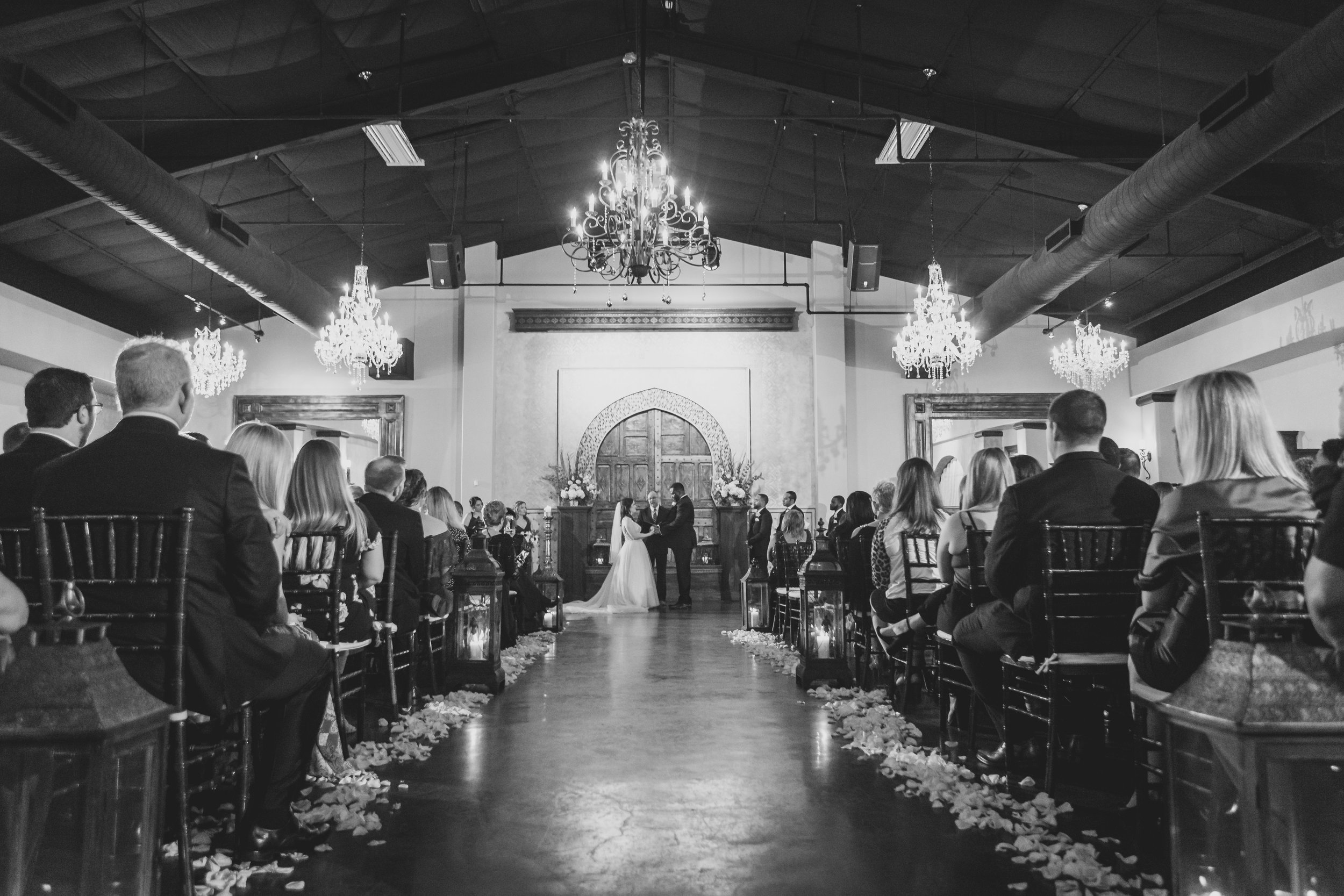 Black and white down the aisle of a bride and groom at the altar.