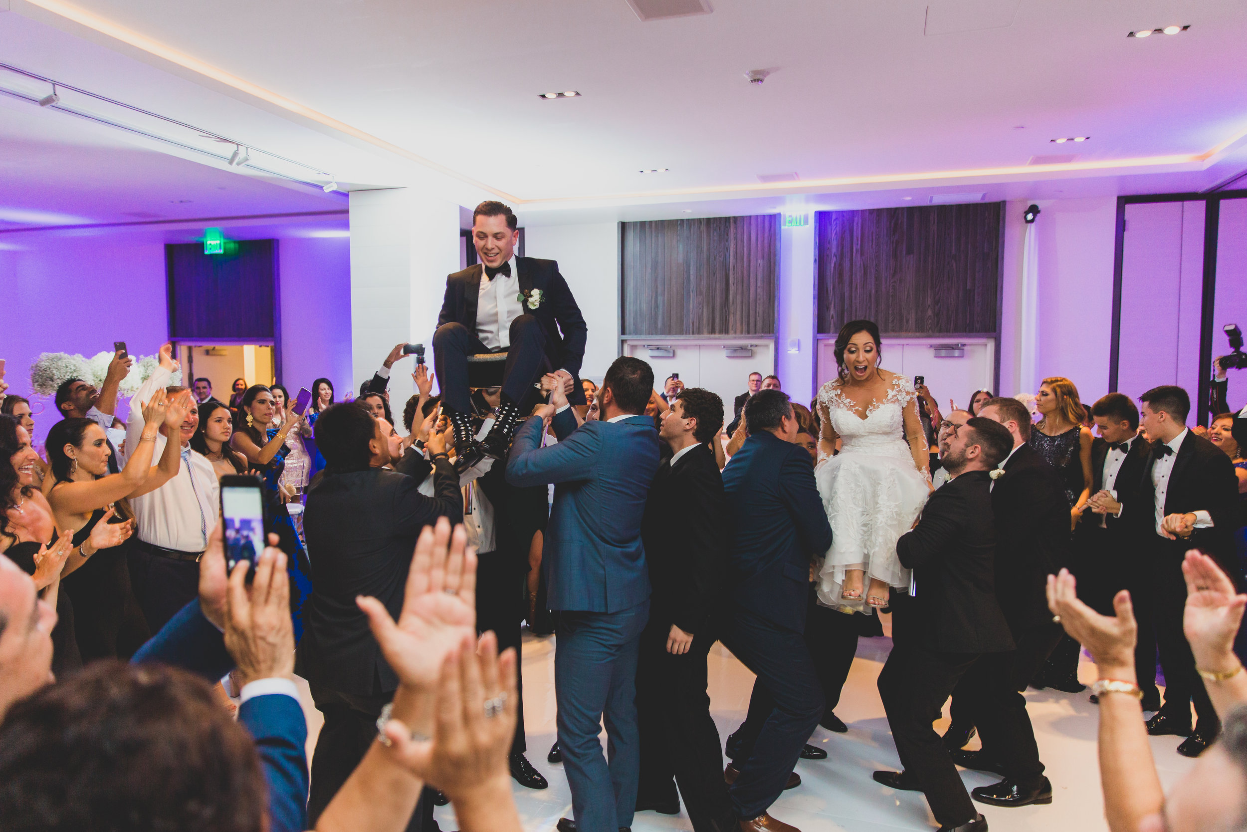 A bride and groom being hoisted into the air on chairs at their wedding.