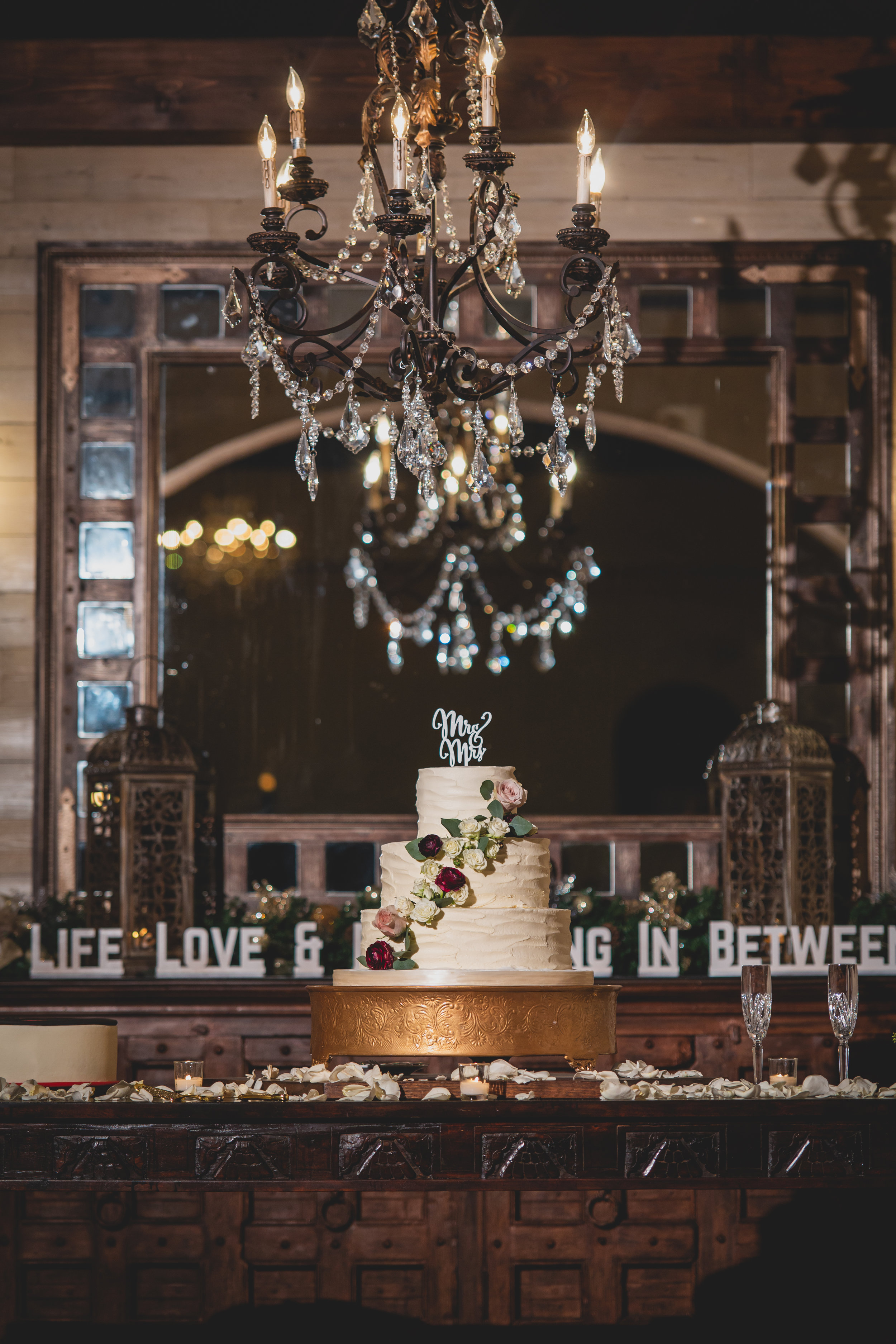 A three tiered white wedding cake under a chandelier.