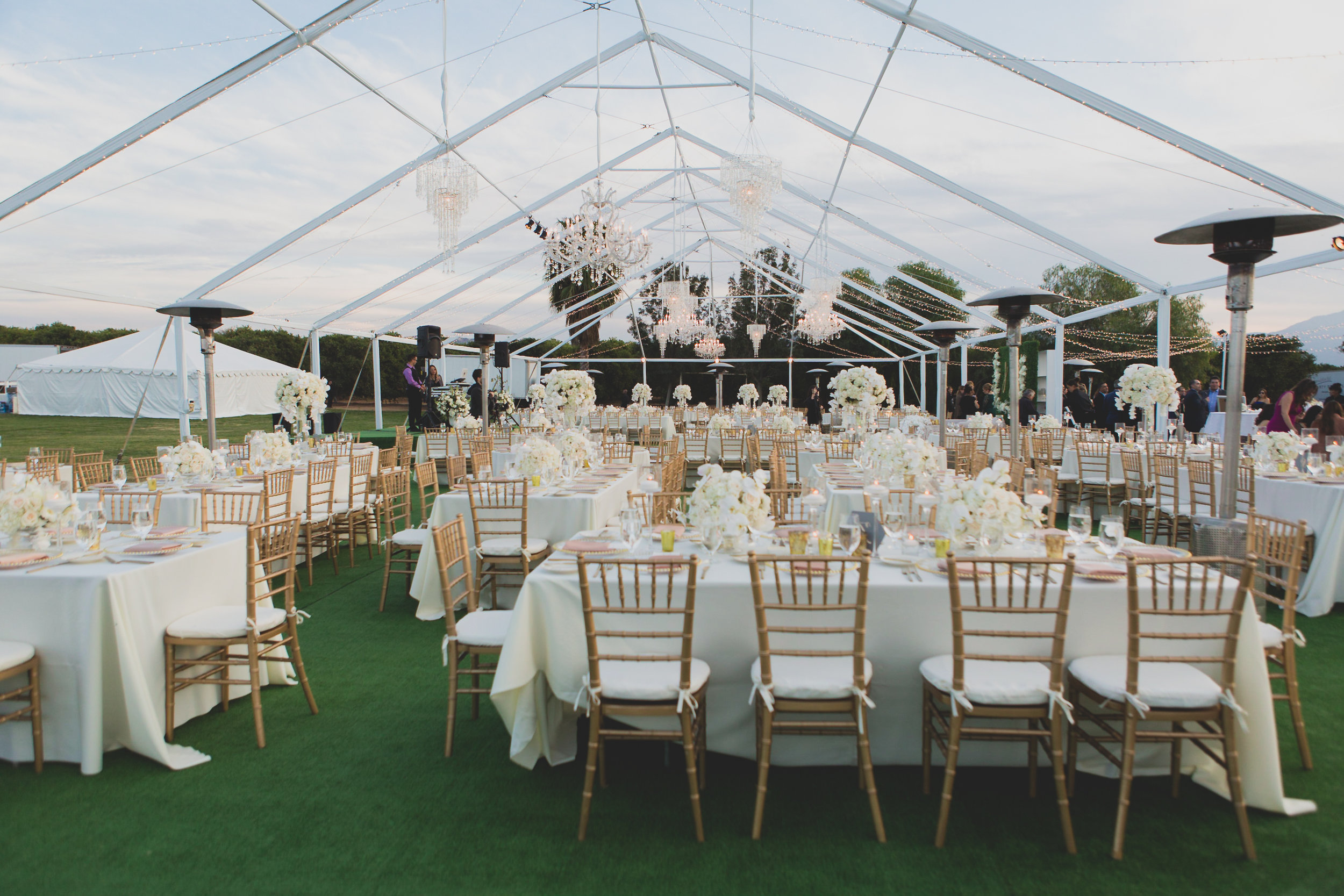 An outdoor venue with a pointed glass roof and tables arranged for a wedding reception.