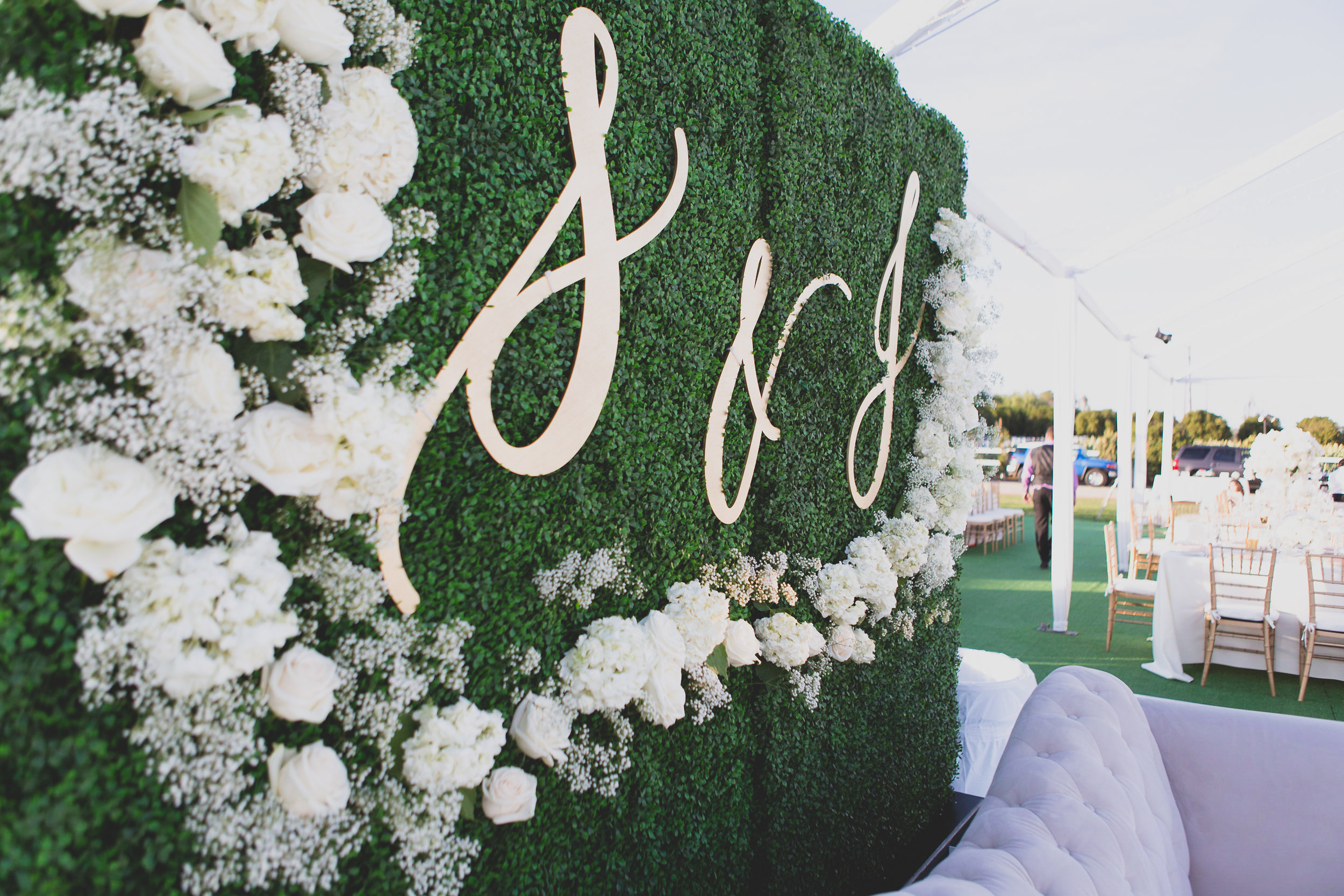 A couch set in front of an ivory wall at an outdoor wedding venue.