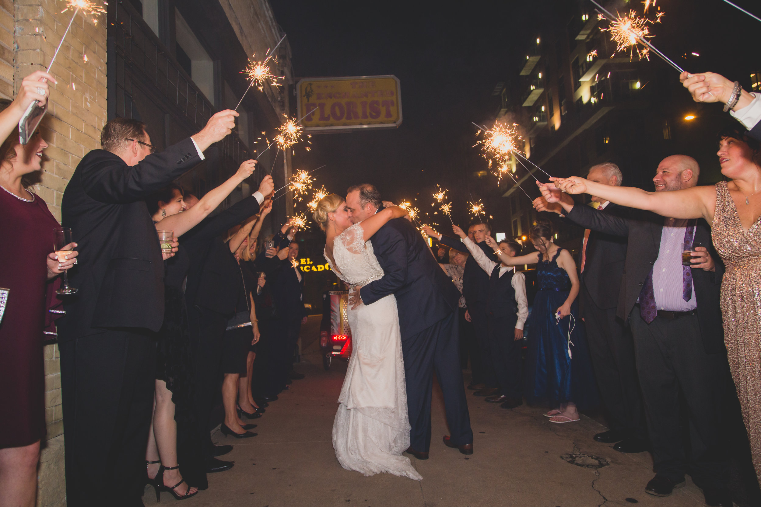 Bride and groom kissing between a human tunnel of sparklers.