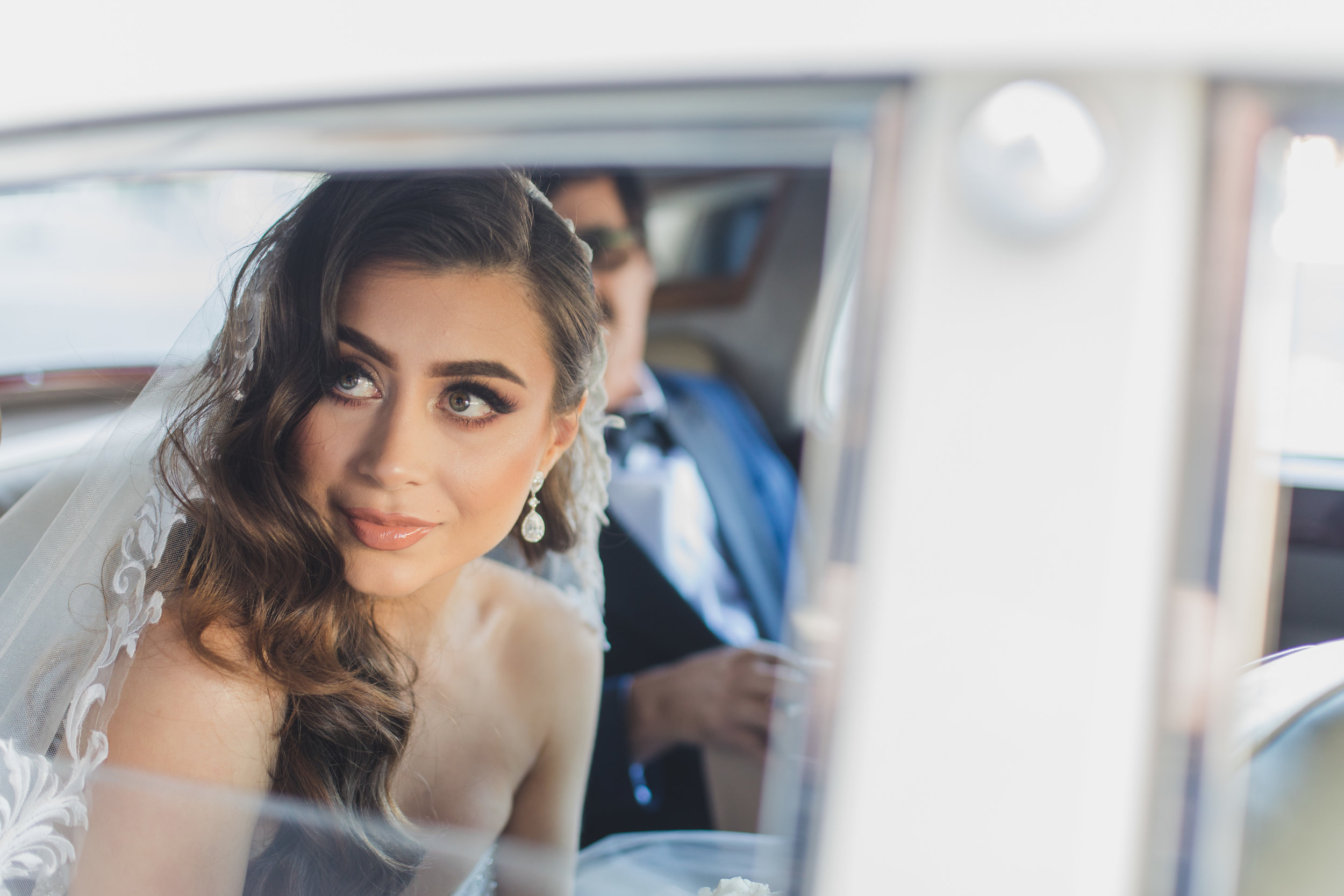 A bride seated in a vintage car and staring through the open window.