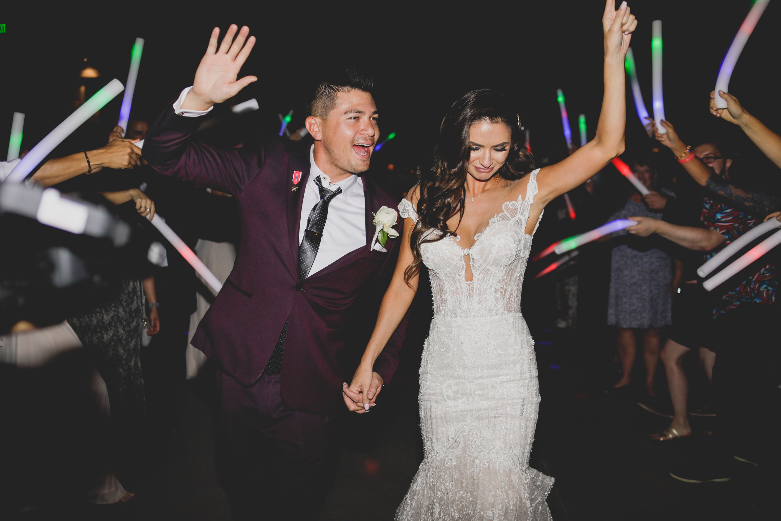 Bride and groom exiting their wedding with raised hands through a sea of glow sticks.
