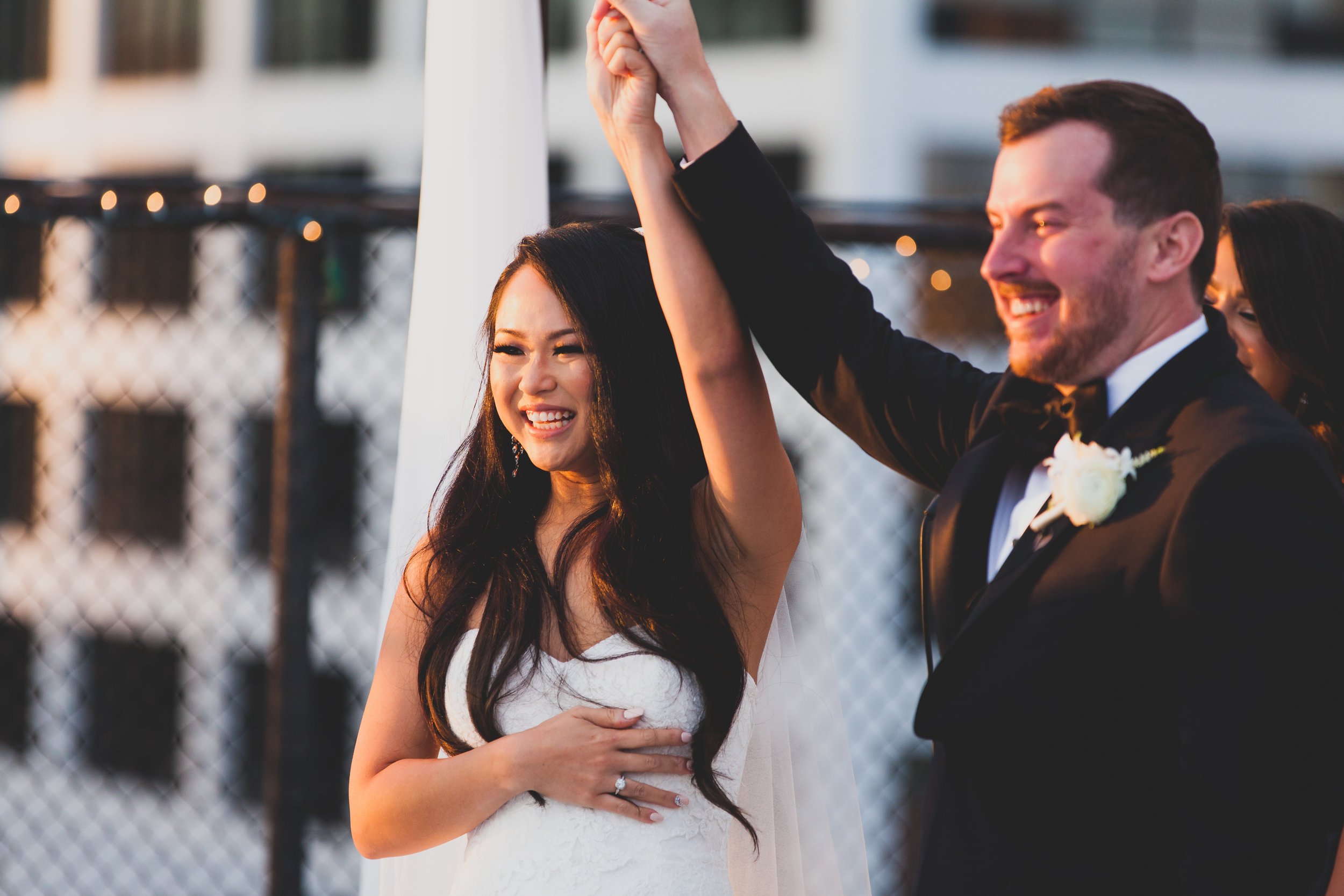 Bride and groom raising their held hands in appreciation.