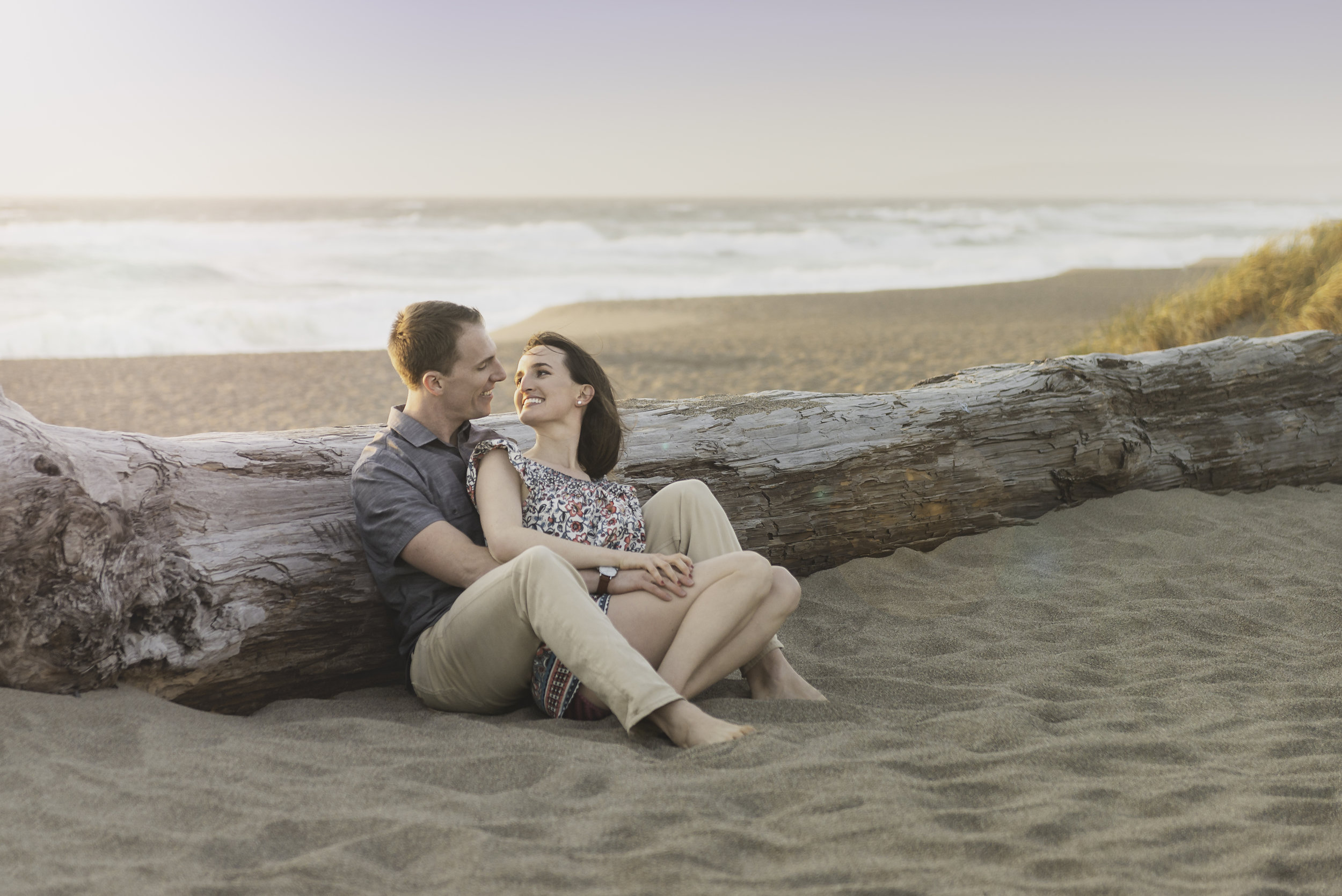 An engaged couple sitting in the sand with their backs to a fallen log that washed ashore.