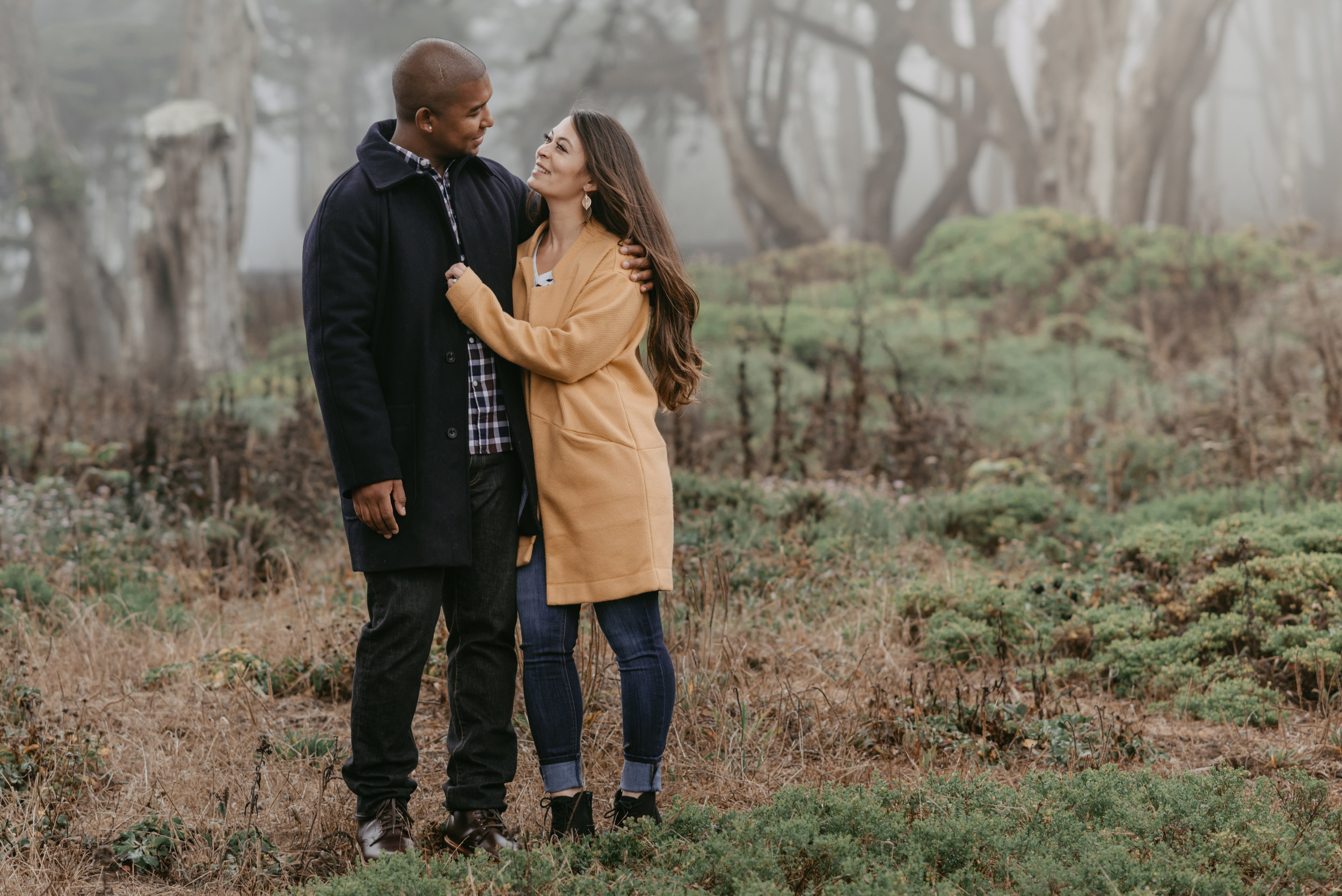 An engaged couple in fall attire grasping one another in a foggy forest.