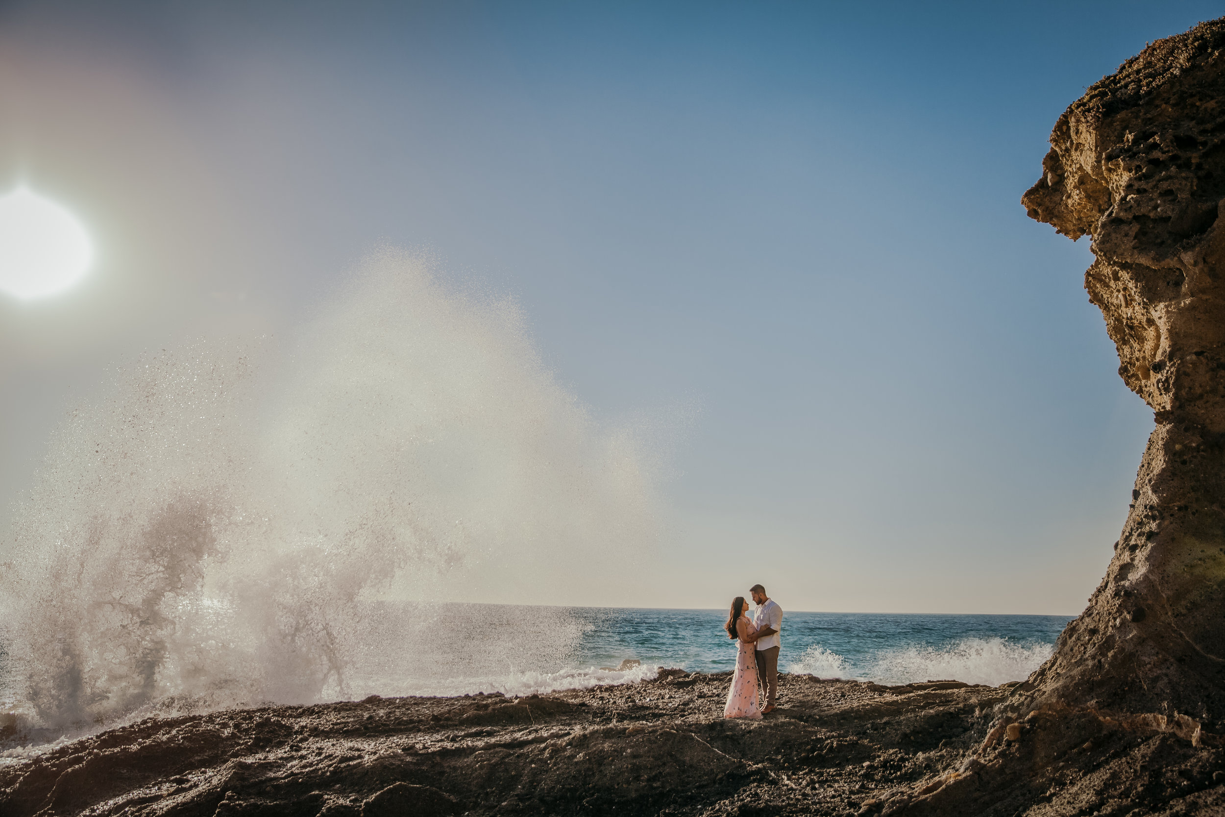 A couple standing on a rocky outcrop as ocean waves crash behind them.