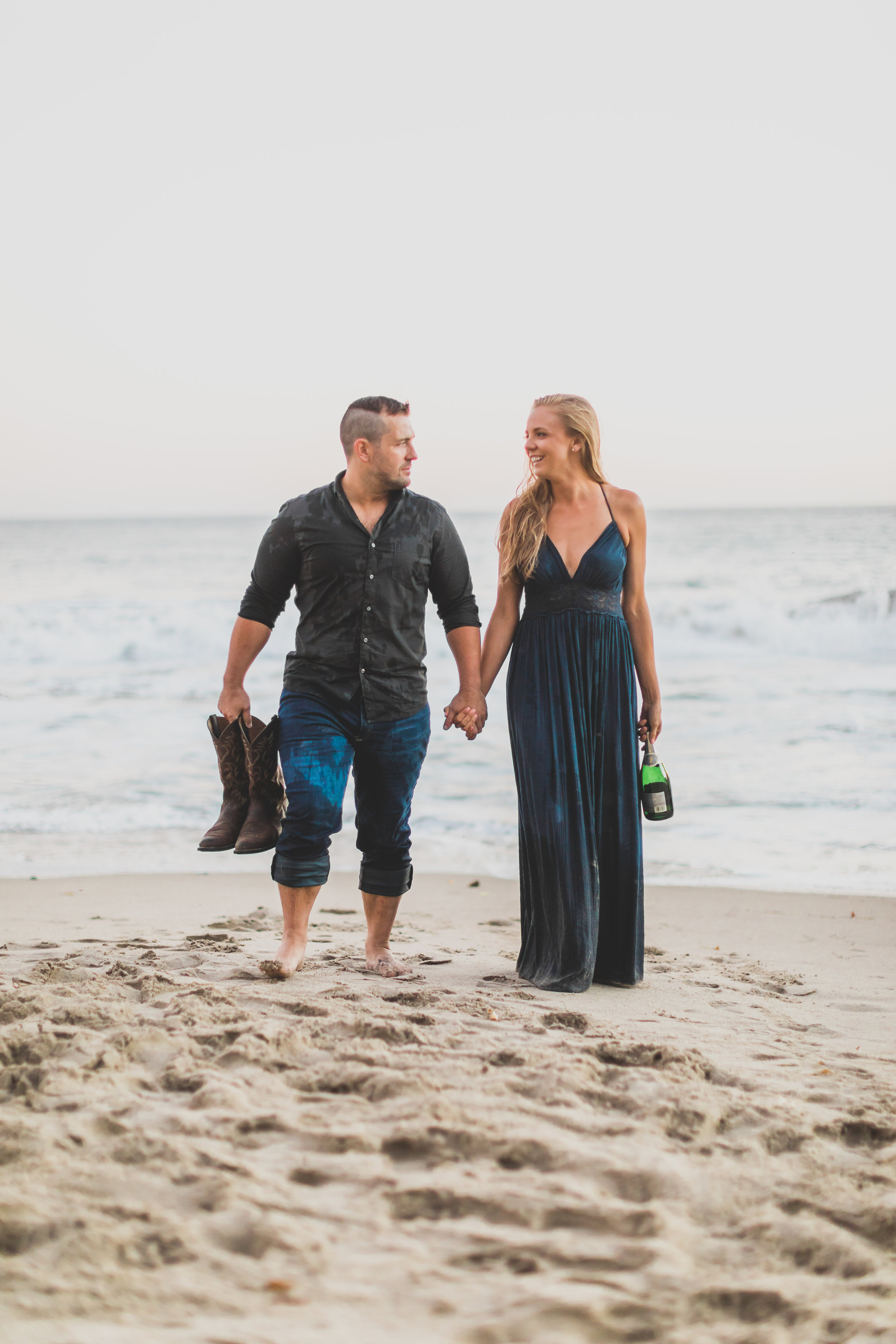 A couple holding their shoes and a champagne bottle as they walk barefoot in the sand.