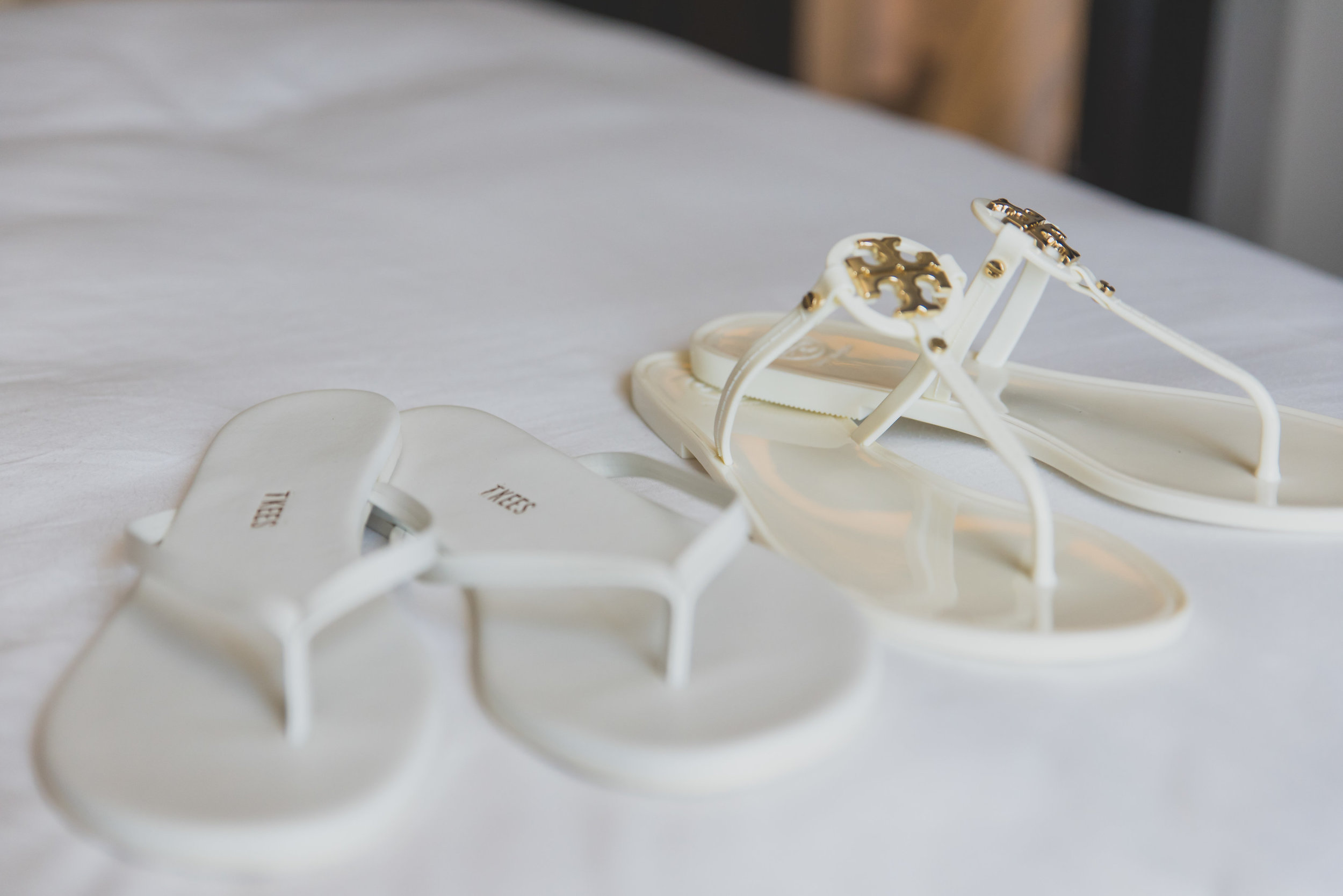 Two pairs of white beach sandals on a white bed.