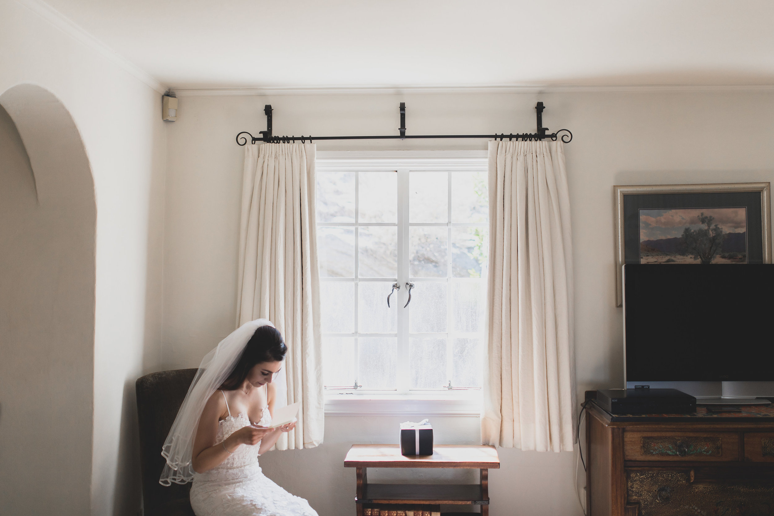 A bride sitting by the window in a room alone reading a letter.
