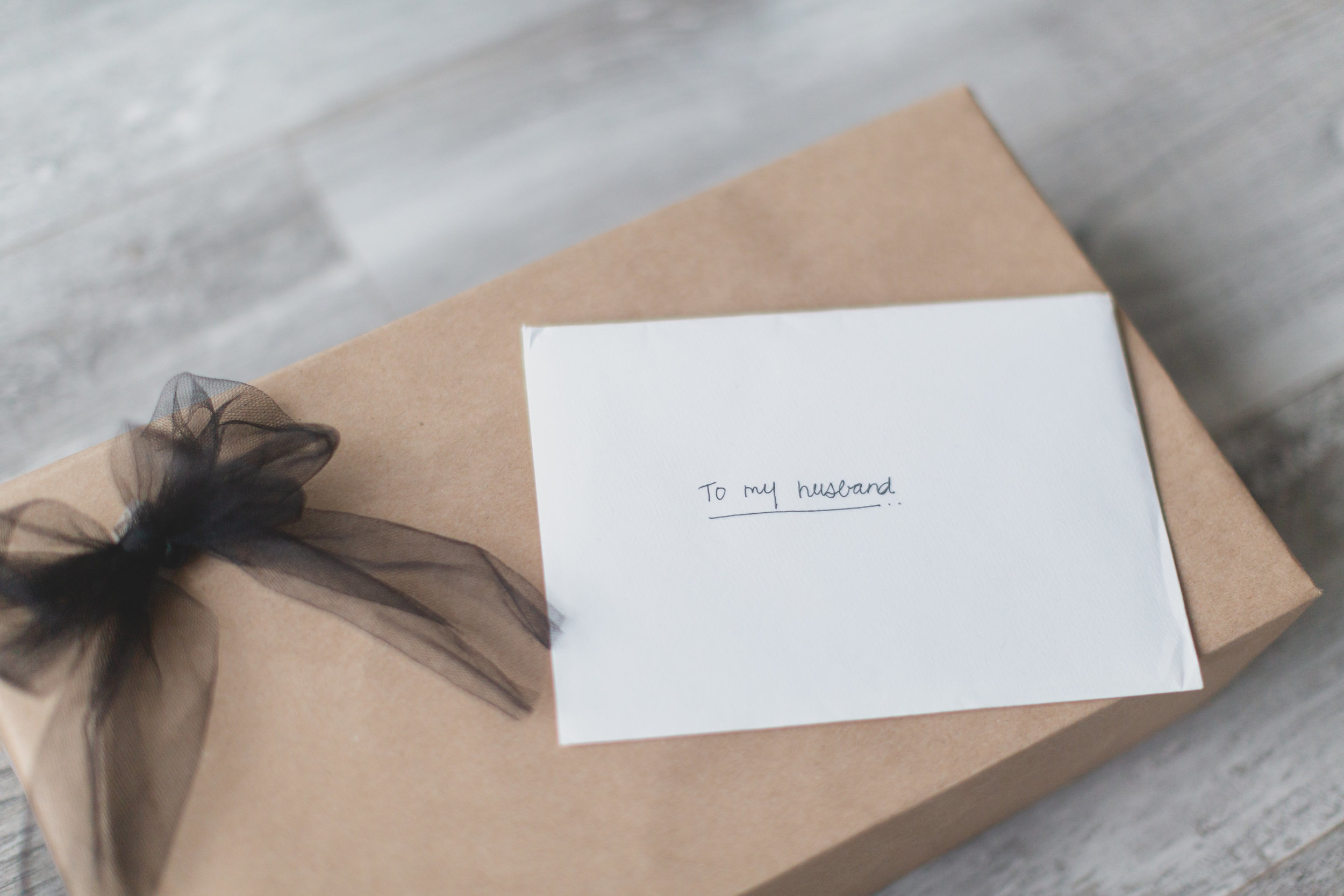 """A nondescript rectangular box with a black bow and a note addressed """"to my husband""""."""