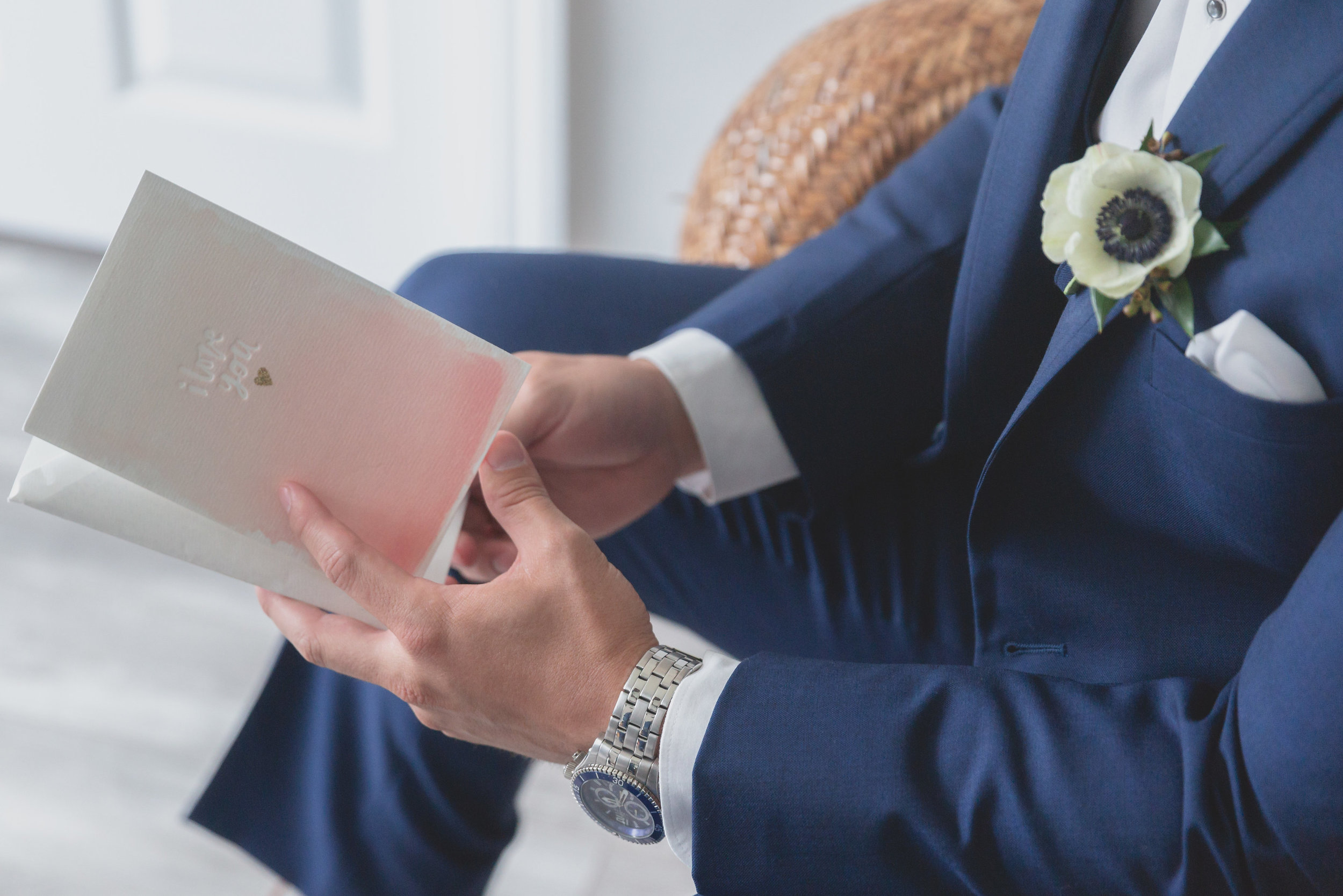 A groom in a navy blue suit and a silver watch reading a letter in a chair.