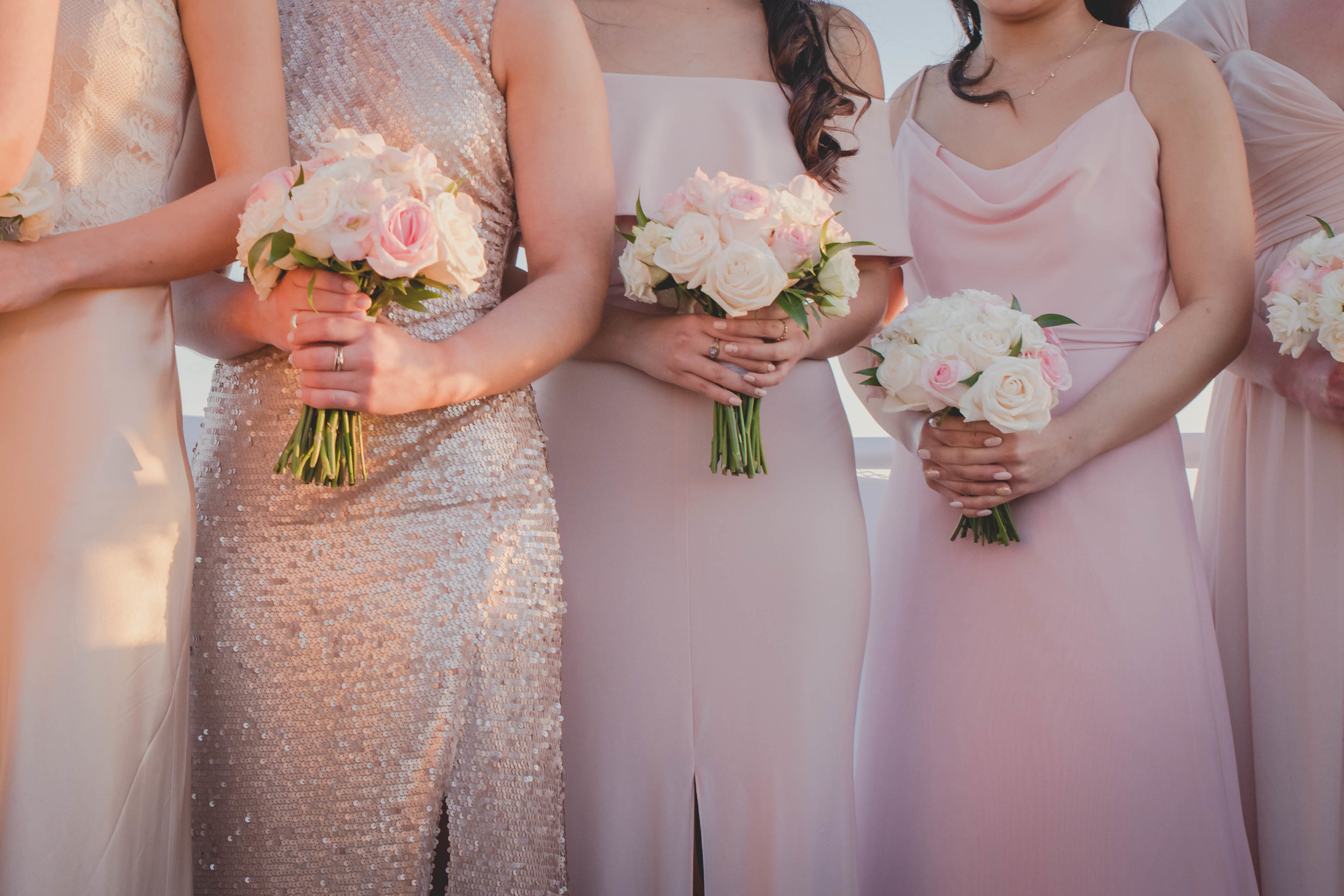 A group of bridesmaids wearing pink and holding pink bouquets.