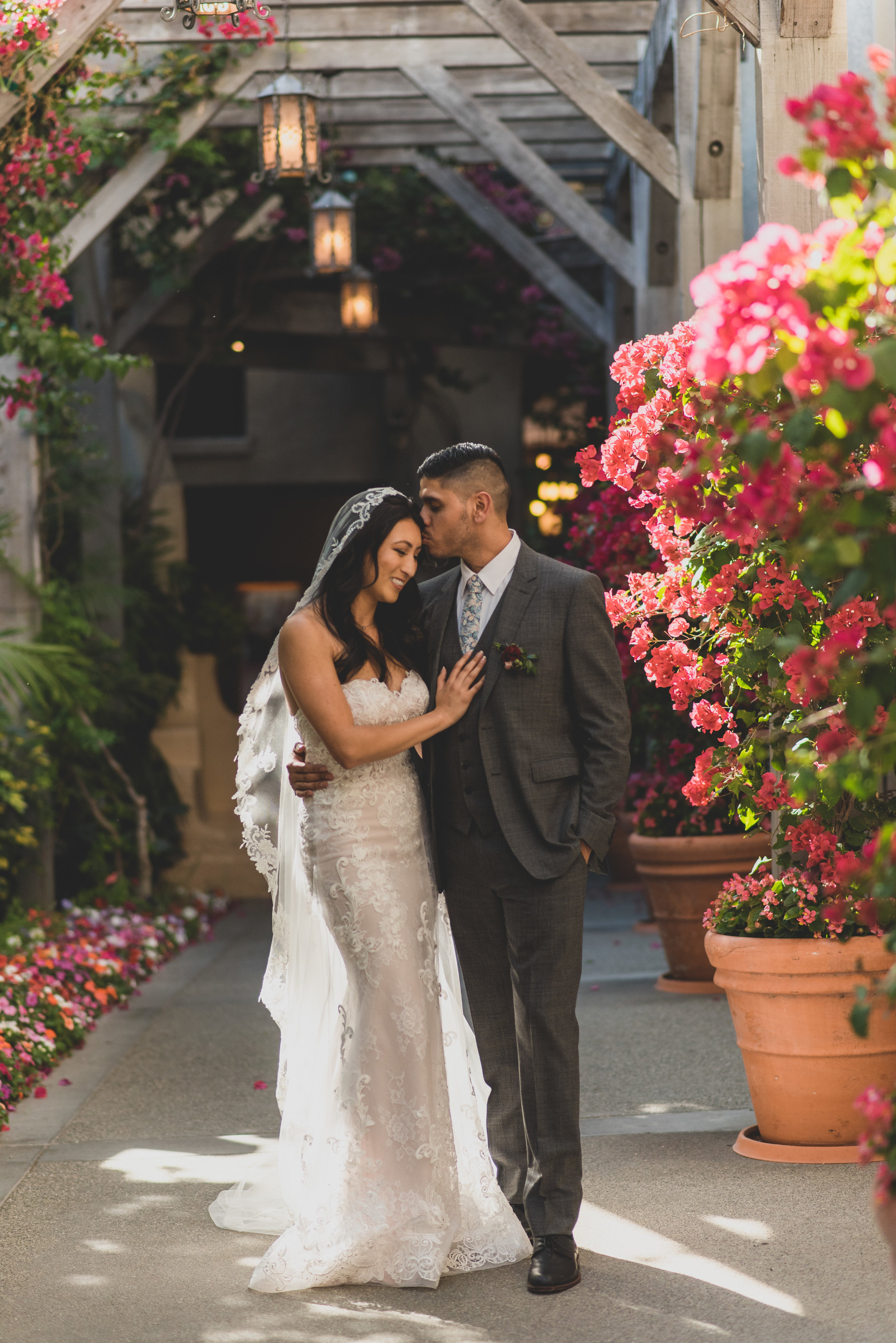 A groom kissing his bride on the forehead in a garden walkway of flowers.