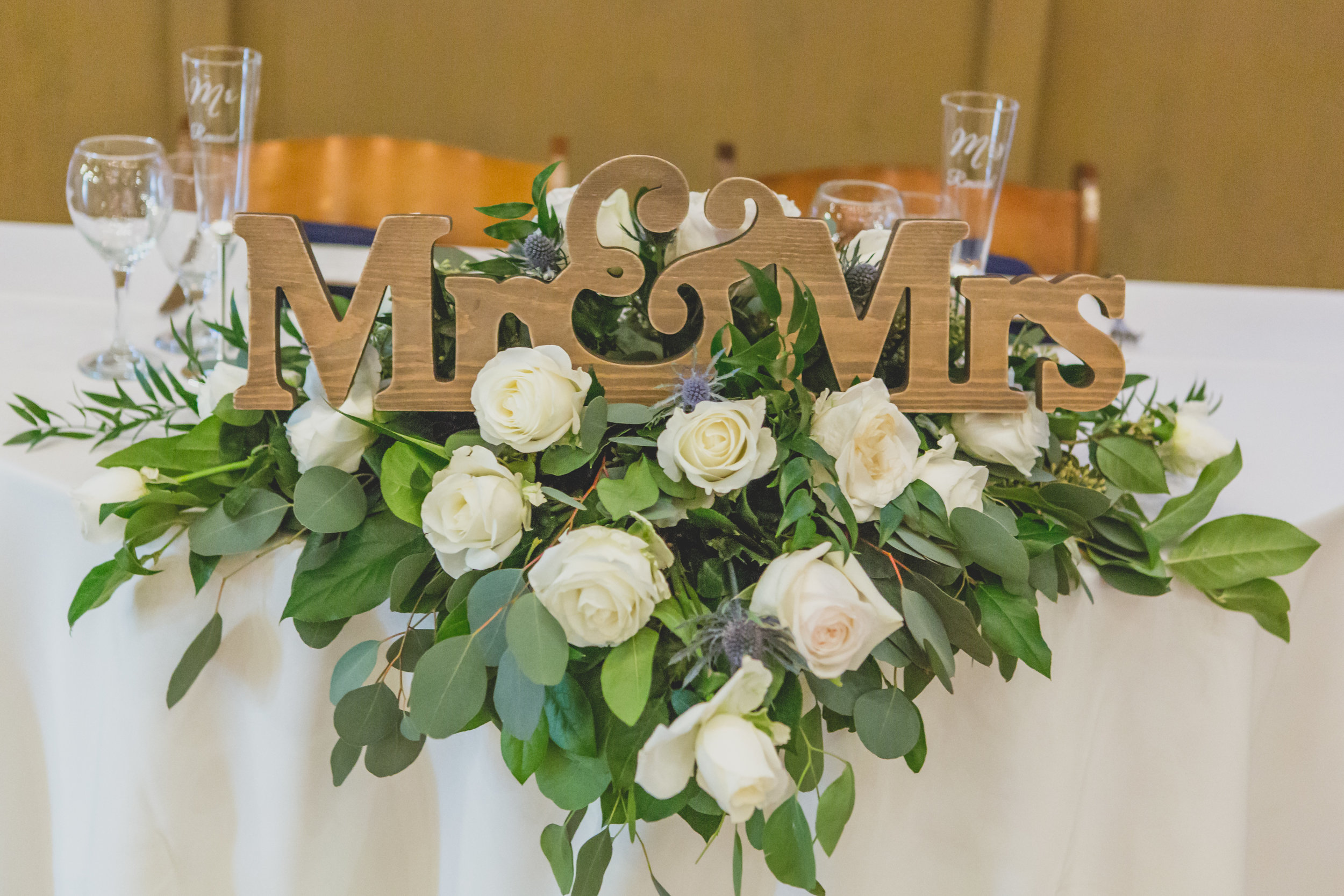 White roses in a lush green arrangement under a Mr. & Mrs. wooden sign.