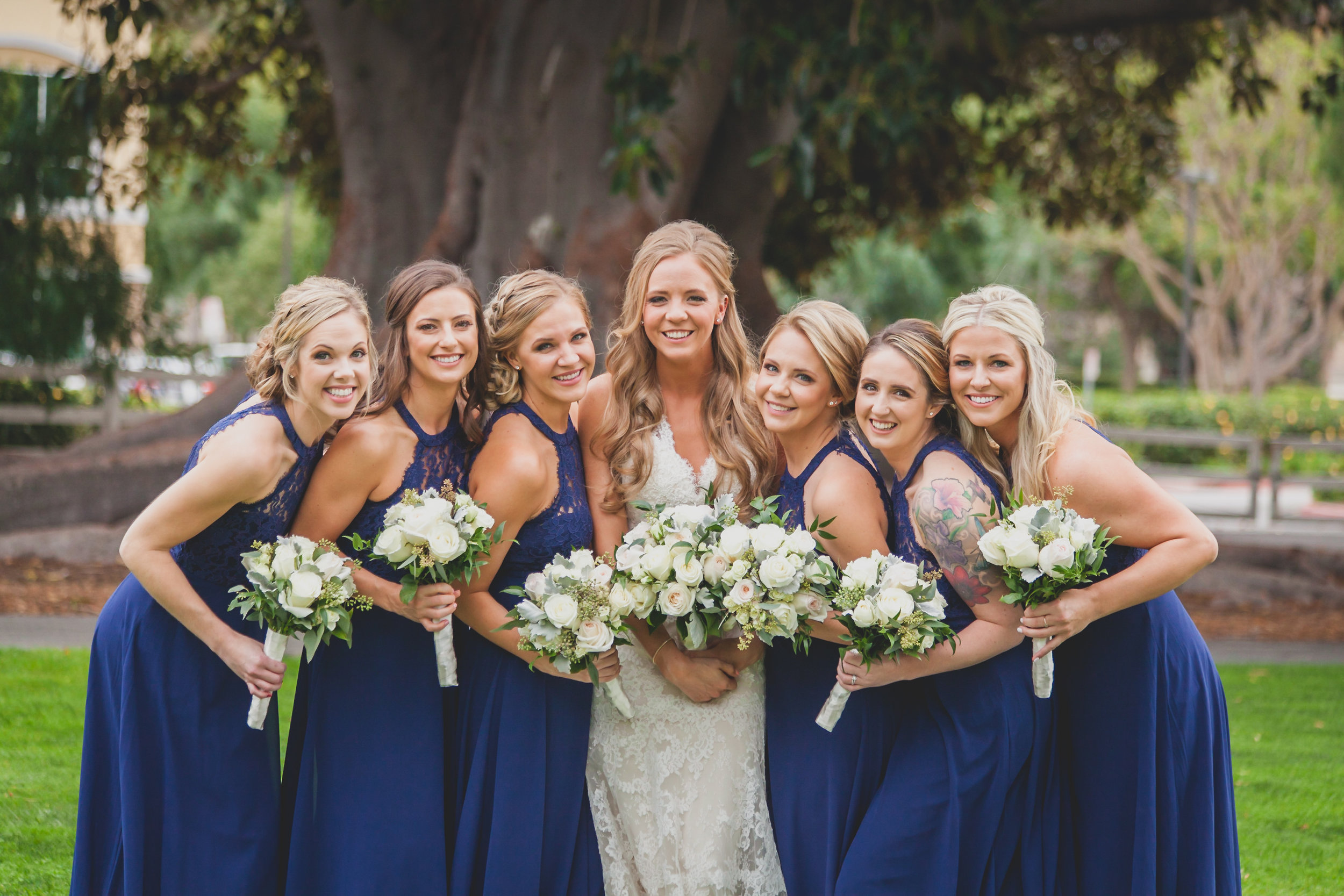 Bridesmaids surrounding the bride holding bouquets of white roses.