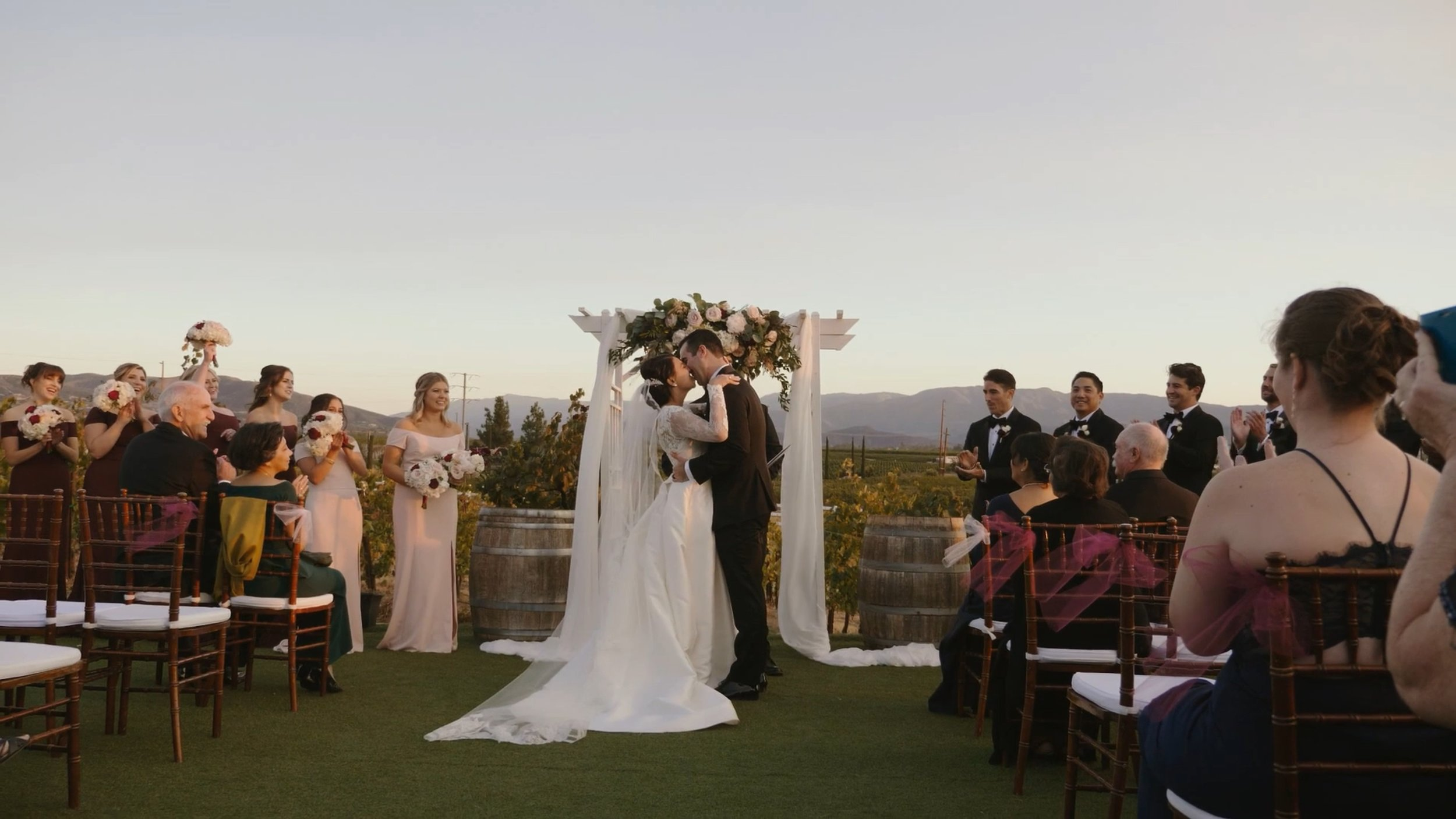 Bride and groom kissing at the altar in front of the rolling hills of a California winery.