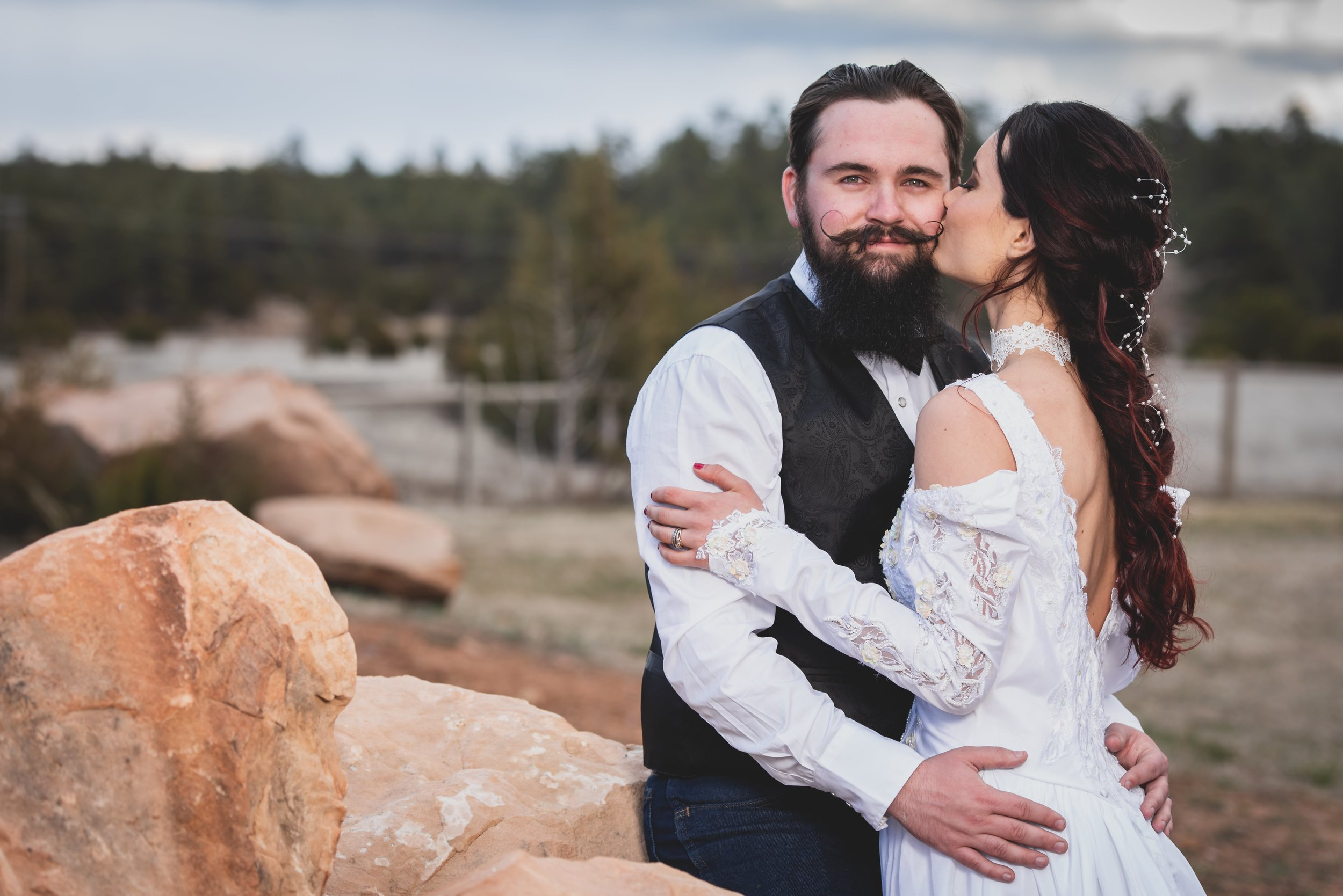 Wedding Photography Arizona - Bride kissing groom on the cheek on a faded red rock.